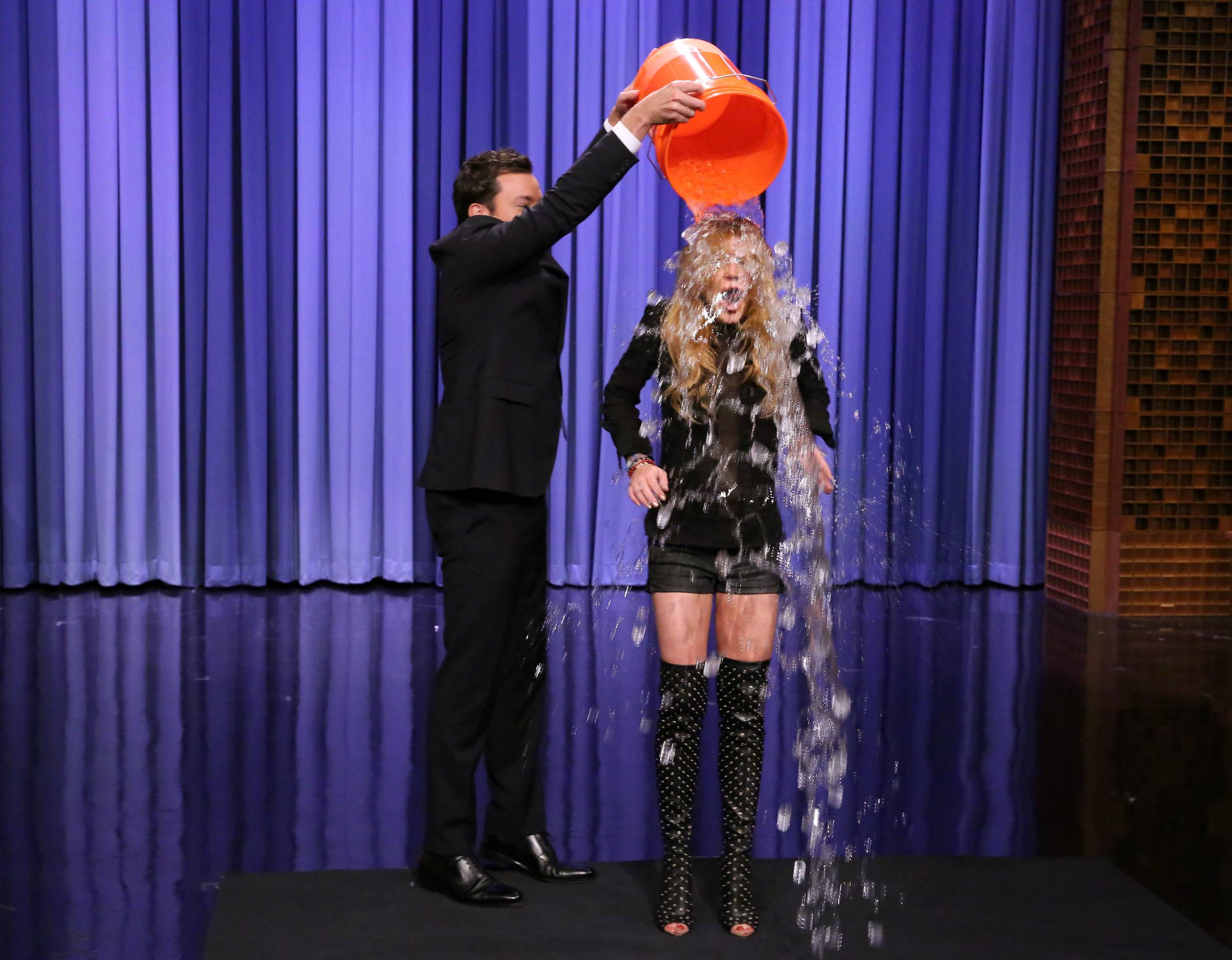 "Jimmy Fallon dumps a bucket of ice water over the head of actress Lindsay Lohan as she participates in the ALS Ice Bucket Challenge on ""The Tonight Show Starring Jimmy Fallon."" The phenomenal success of the fundraising craze is making charitable organizations rethink how they connect with a younger generation of potential donors, specifically through social media."