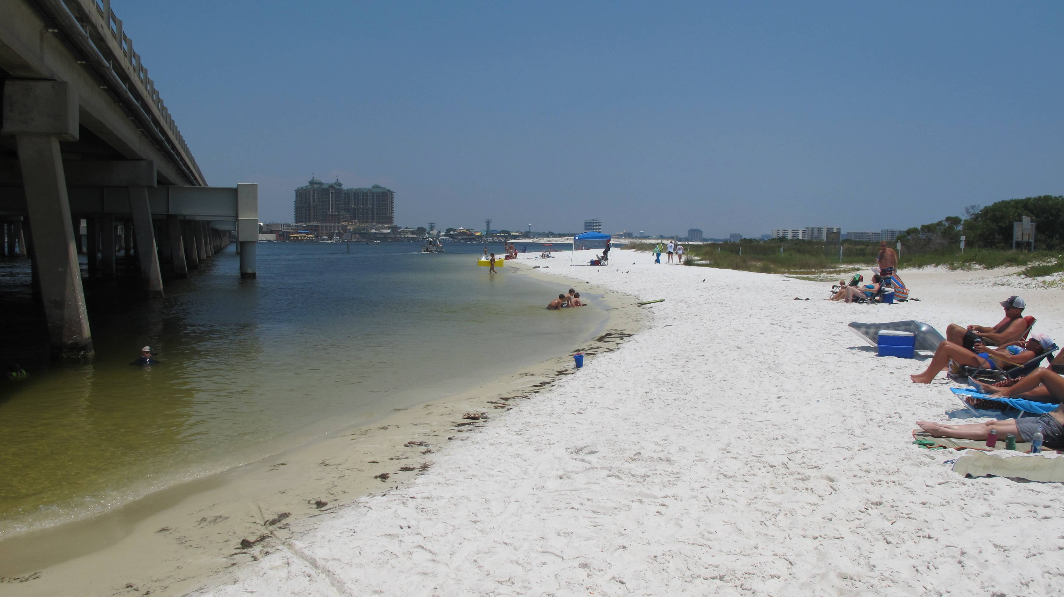 Beachgoers enjoy the shallow beach under a highway bridge in Destin, Fla. The beach is under the control of Eglin Air Force Base where it is occasionally used to practice amphibious landings and test high-tech weapons. The public is welcome to use the beach.