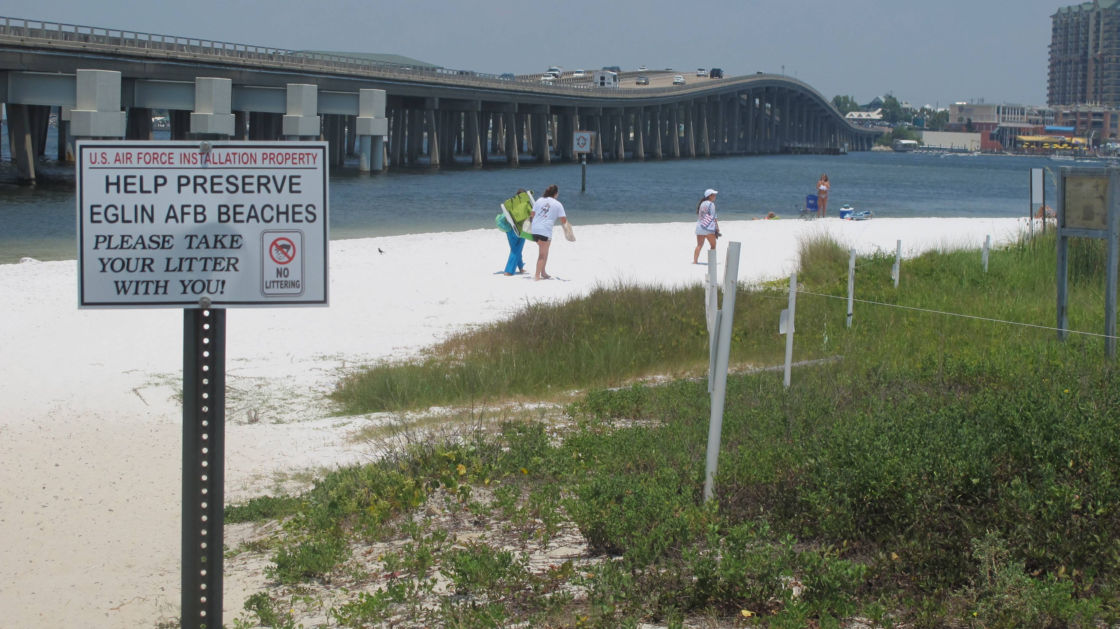 People look for a place to set up on a shallow beach under a highway bridge in Destin, Fla. Eglin Air Force Base controls the beach, but a small section of the beach is open to the public.