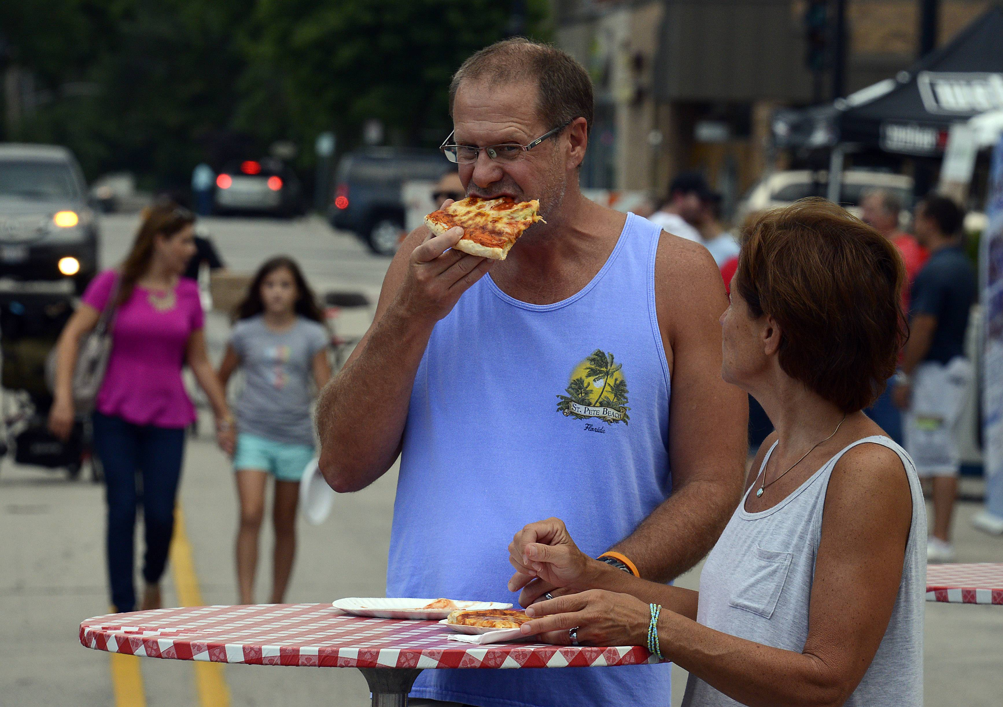 Kerry and Karen Richardson of Palatine chow down on pizza at the Palatine Street Fest on Friday.