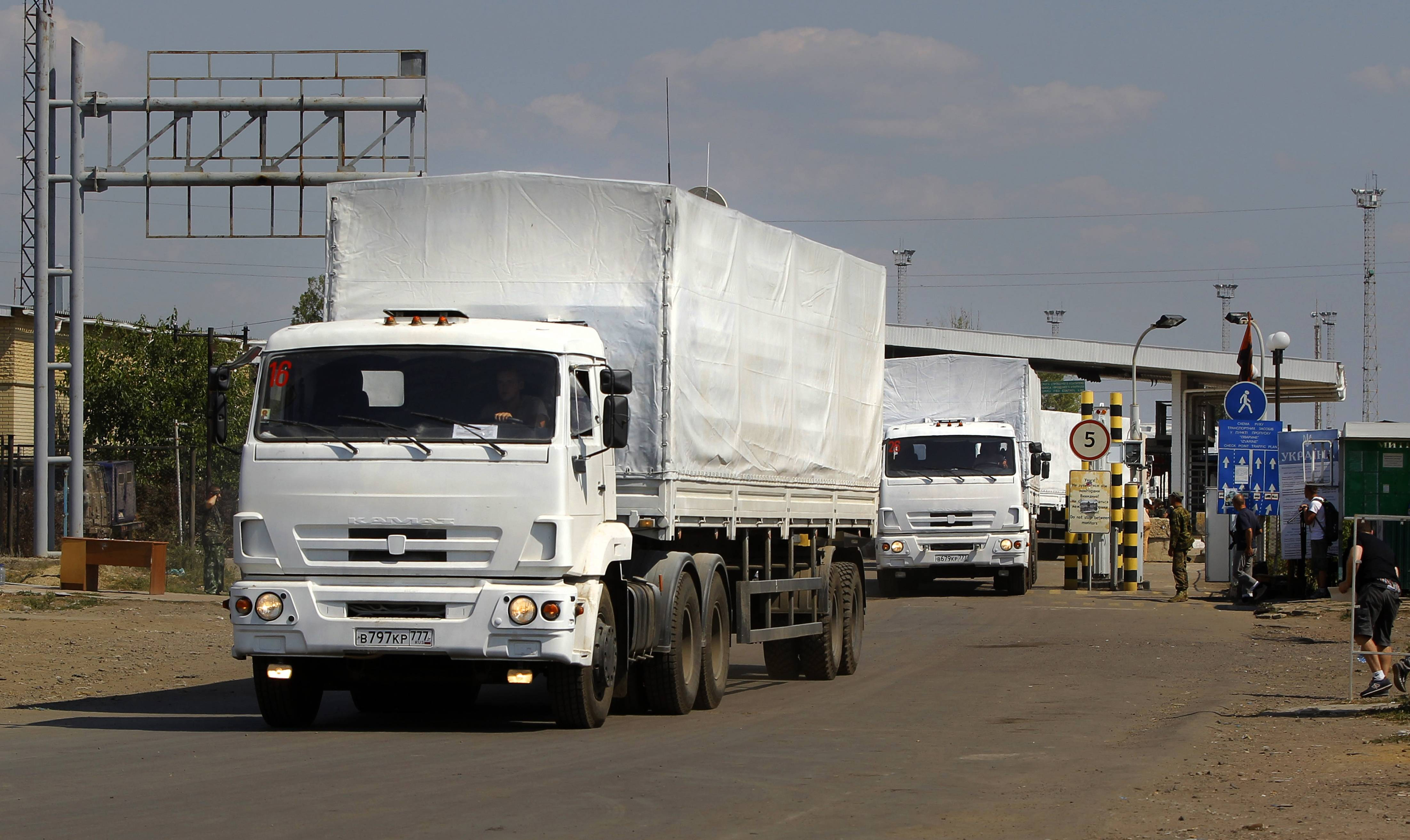 The first trucks of the aid convoy pass the border post Friday at Izvaryne, eastern Ukraine.