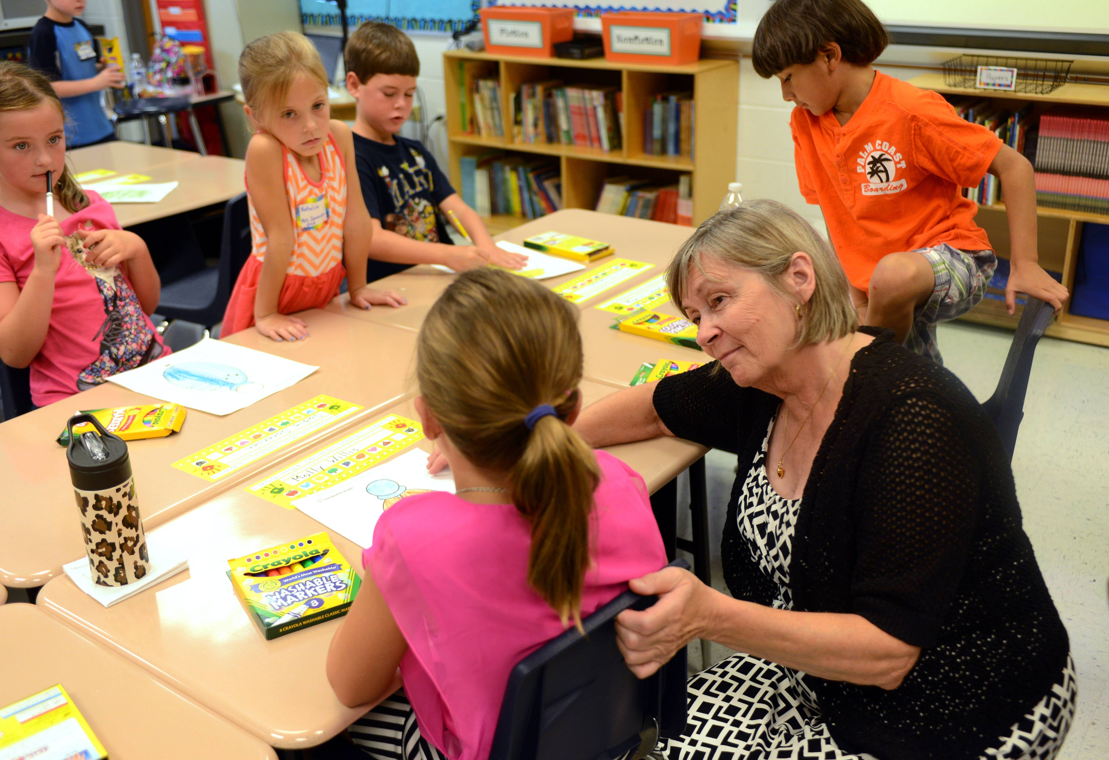 Oak Grove Elemenntary School second grade teacher Marie Sorensen works with students Friday on the first day of classes in Green Oaks. Sorensen is retiring at the end of this school year after 26 years of teaching at the school.