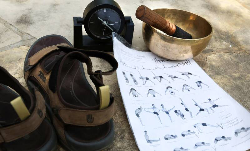 Damasius' sandals, timer, Tibetan singing bowls and Ashtanga yoga position sheet sit nearby during a class.