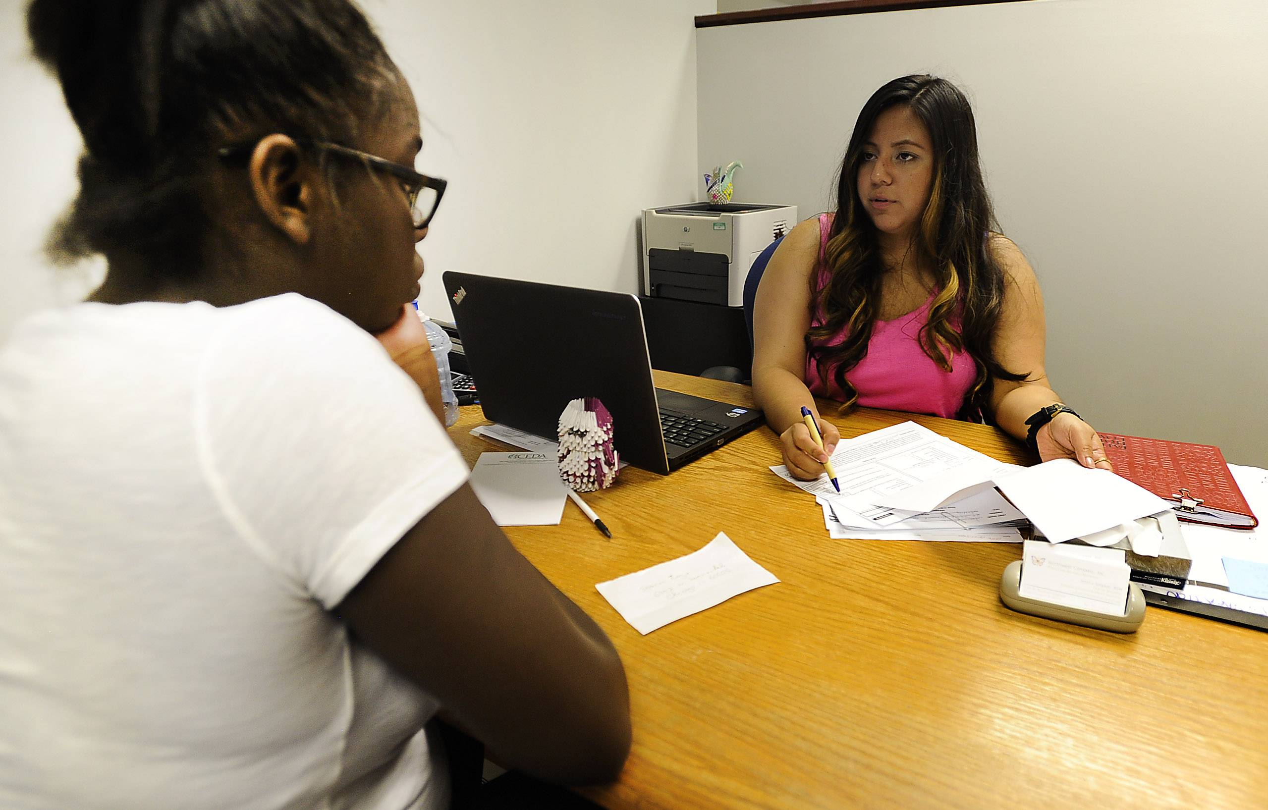 Jessica Salgado, a hardship intervention specialist, speaks with Annette Barner of Schiller Park in her office at Northwest Compass, formally CEDA Northwest, which focuses on helping people in need.
