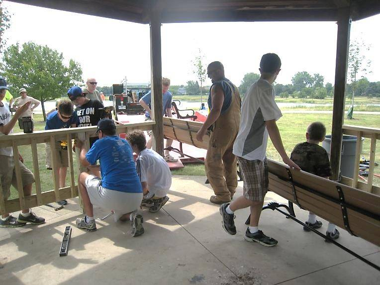 Troop 32 scouts and leaders carry in new benches and assemble rails for the Lake Arlington gazebo.
