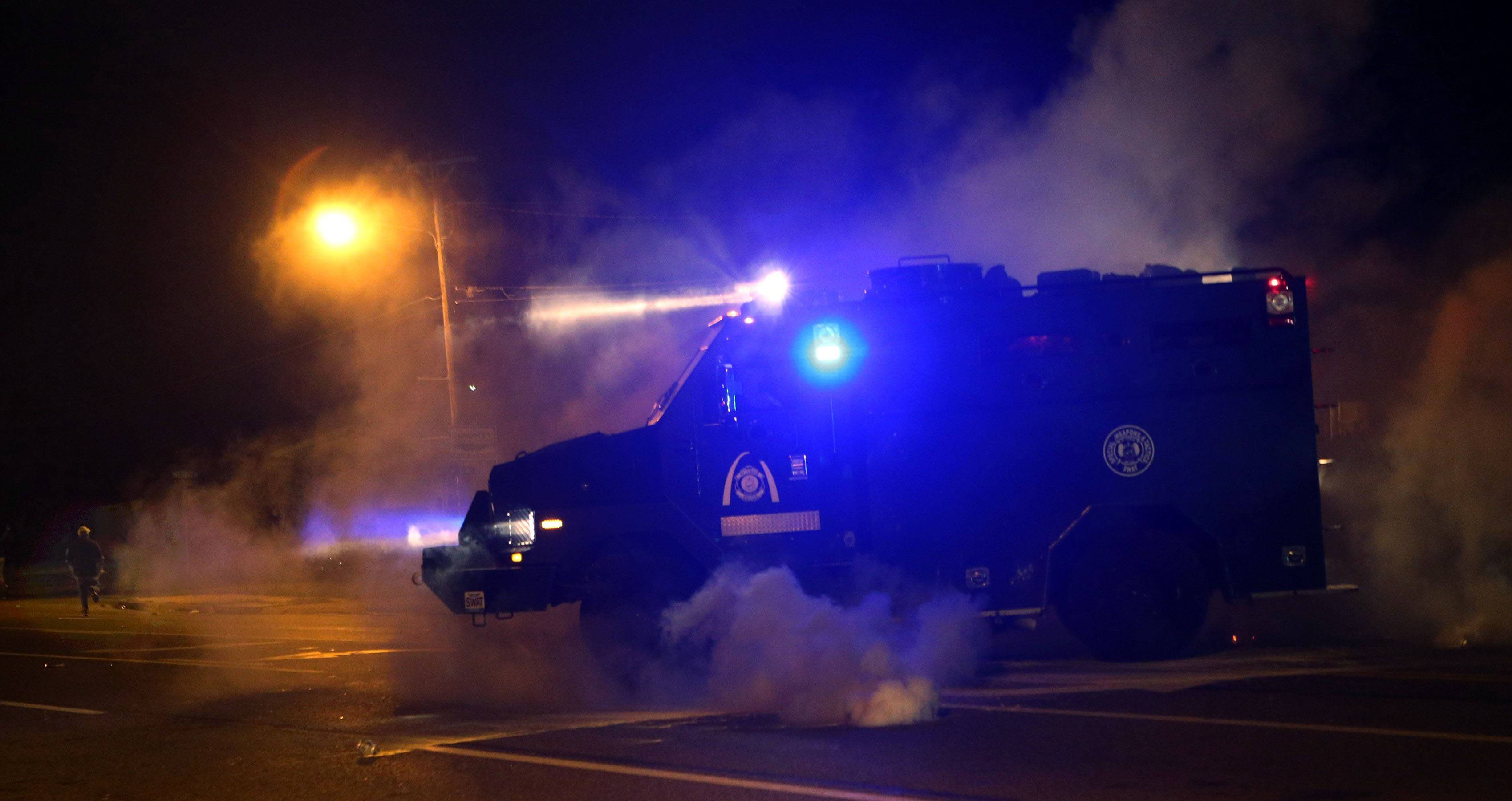 A tactical trucks moves down the street last Sunday through tear gas in Ferguson, Mo.
