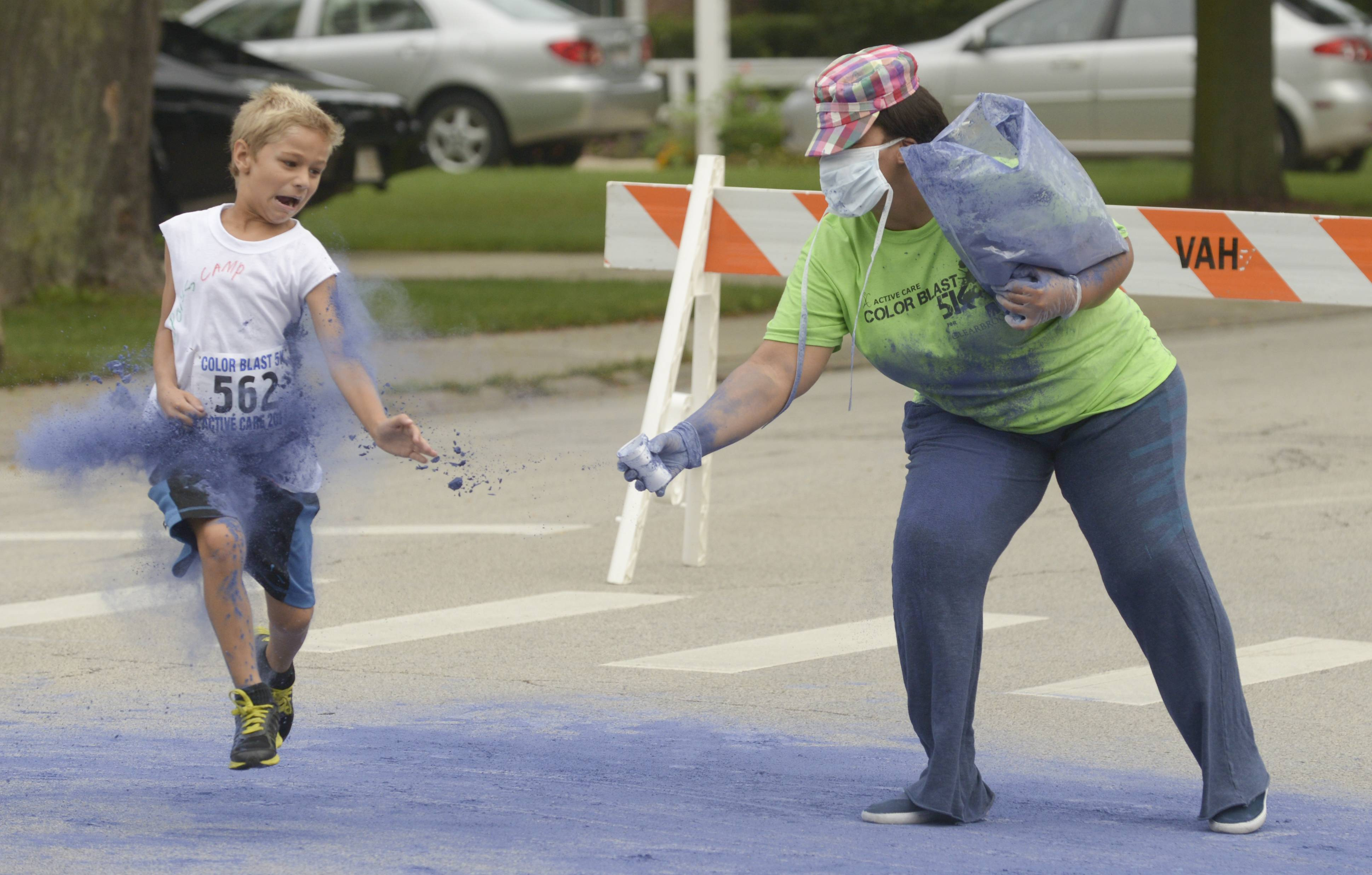 Darsheta Epting of Oak Park tosses blue colored cornstarch powder on a young runner who tries to avoid the toss Saturday during the 2nd annual Active Care ColorBlast 5K in Arlington Heights to support Clearbrook.