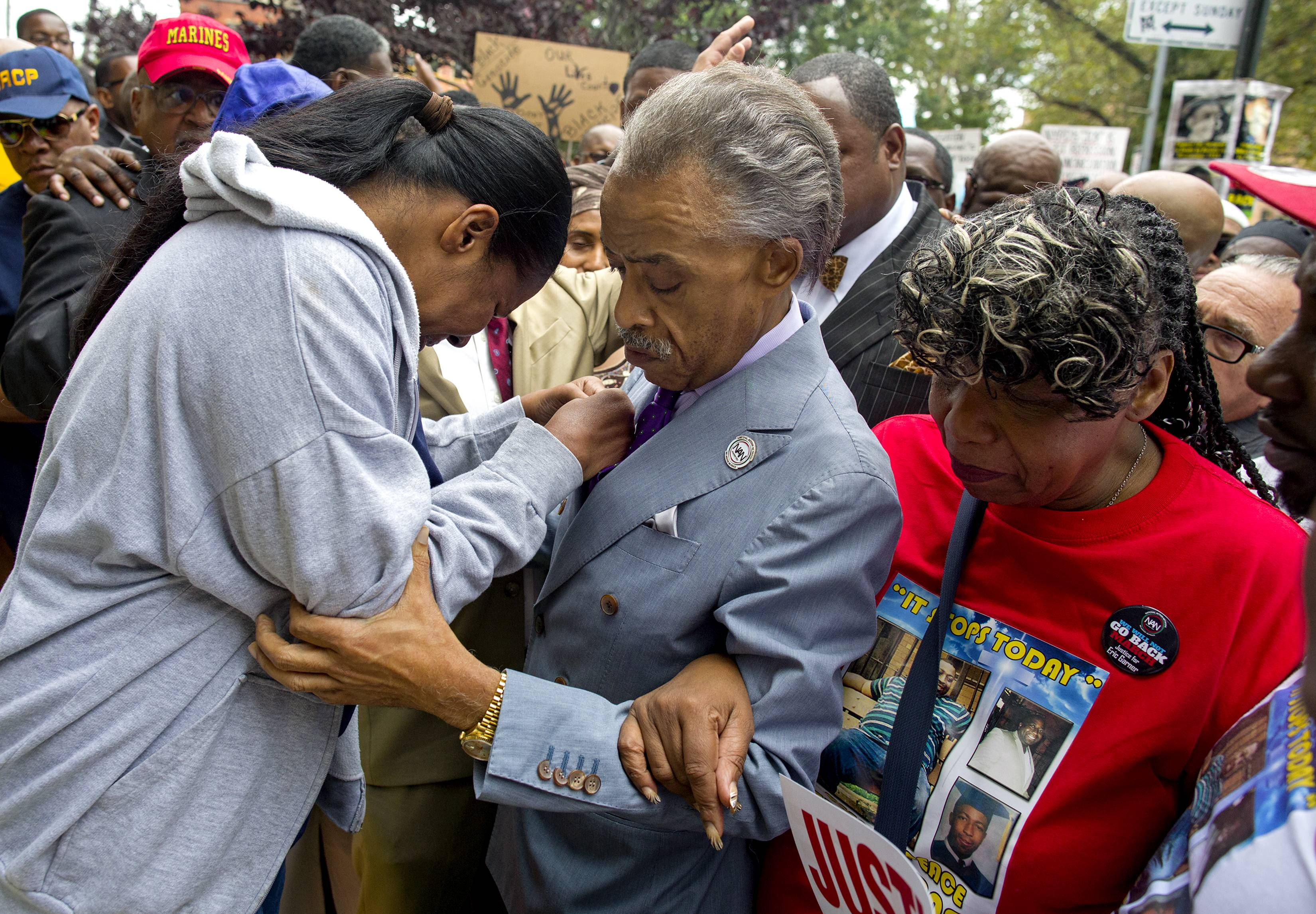 Esaw Garner, left, arrives at the spot where her husband Eric Garner died with The Rev. Al Sharpton, center, and Eric Garner's mother Gwen Carr, right, at the start of a march and rally Saturday in the Staten Island borough of New York.