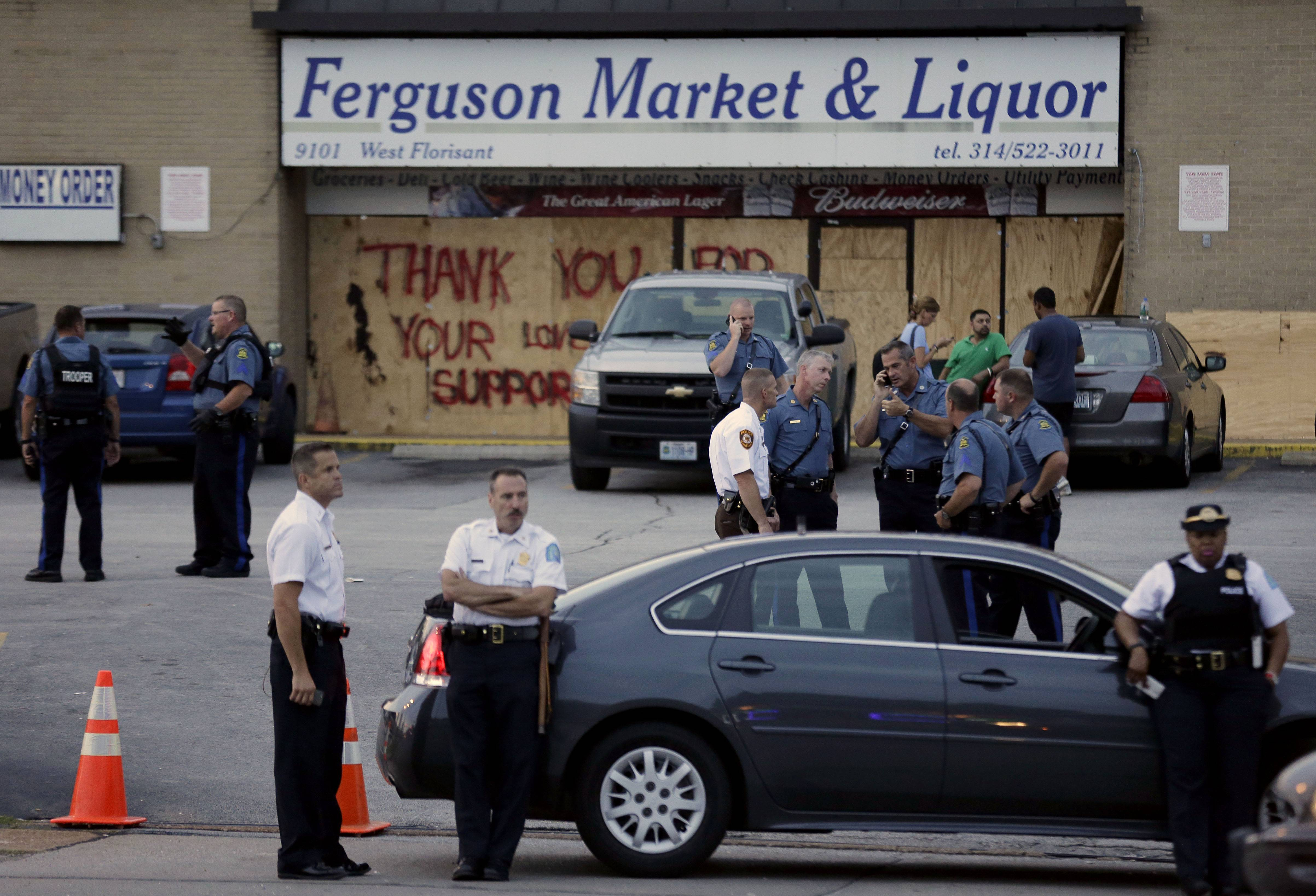 Police stand watch in front of a market in Ferguson, Missouri. Life in this working-class St. Louis suburb of modest brick homes and low-rise apartments hasn't been the same since the shooting of Michael Brown by police.