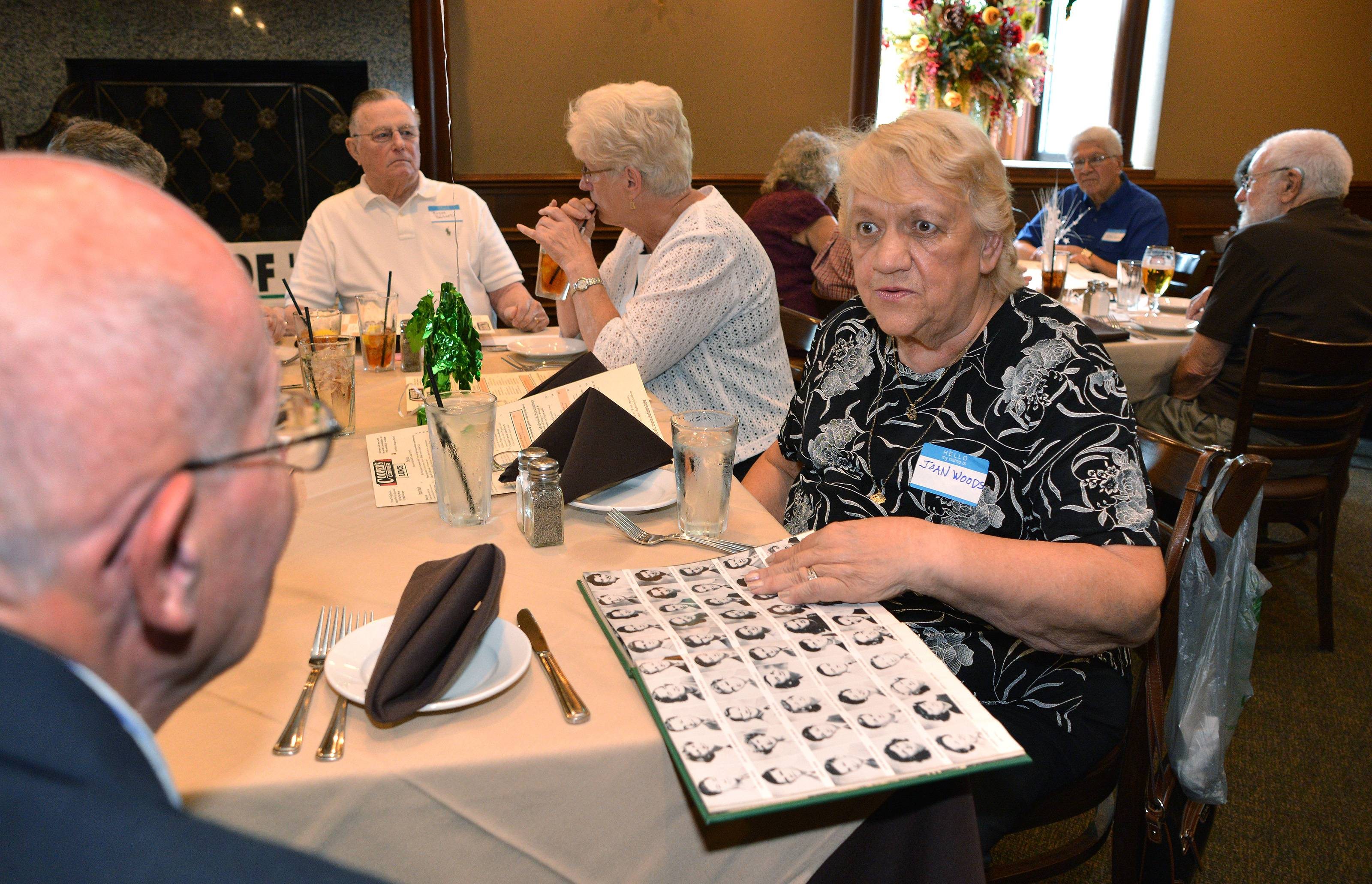 Glenbard West High School Class of 1952 graduates Cal Smith, left, and Joan Woods look at photos in her yearbook during a reunion Friday in Winfield. Roughly 25 classmates came to a luncheon at Cooper's Corner restaurant to celebrate their 80th birthdays.