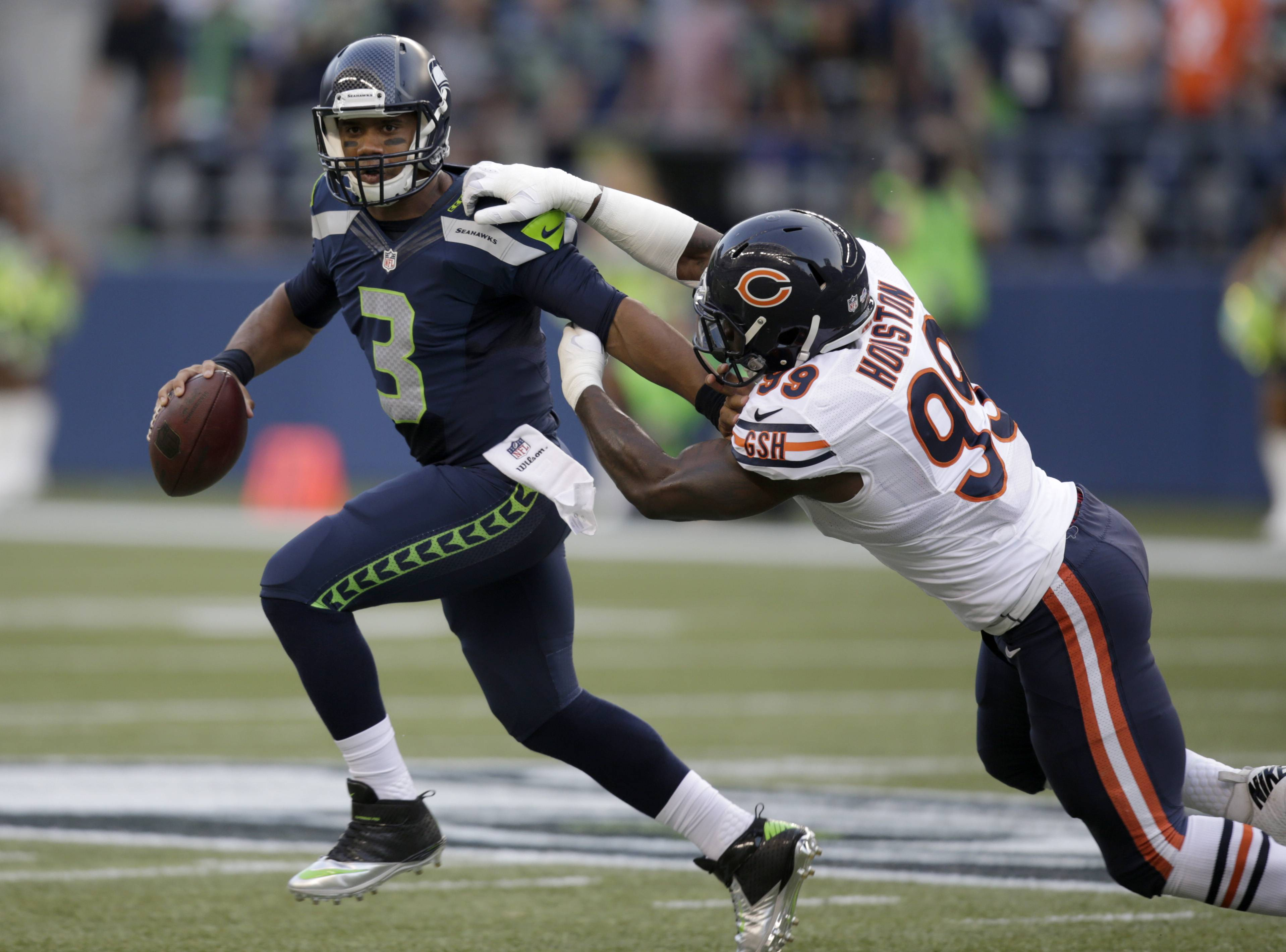 Seattle Seahawks quarterback Russell Wilson (3) tries to escape the grasp of Chicago Bears defensive end Lamarr Houston. The defensive unit was able to pressure Wilson, but it only sacked him once in Friday night's 34-6 loss to Seattle.