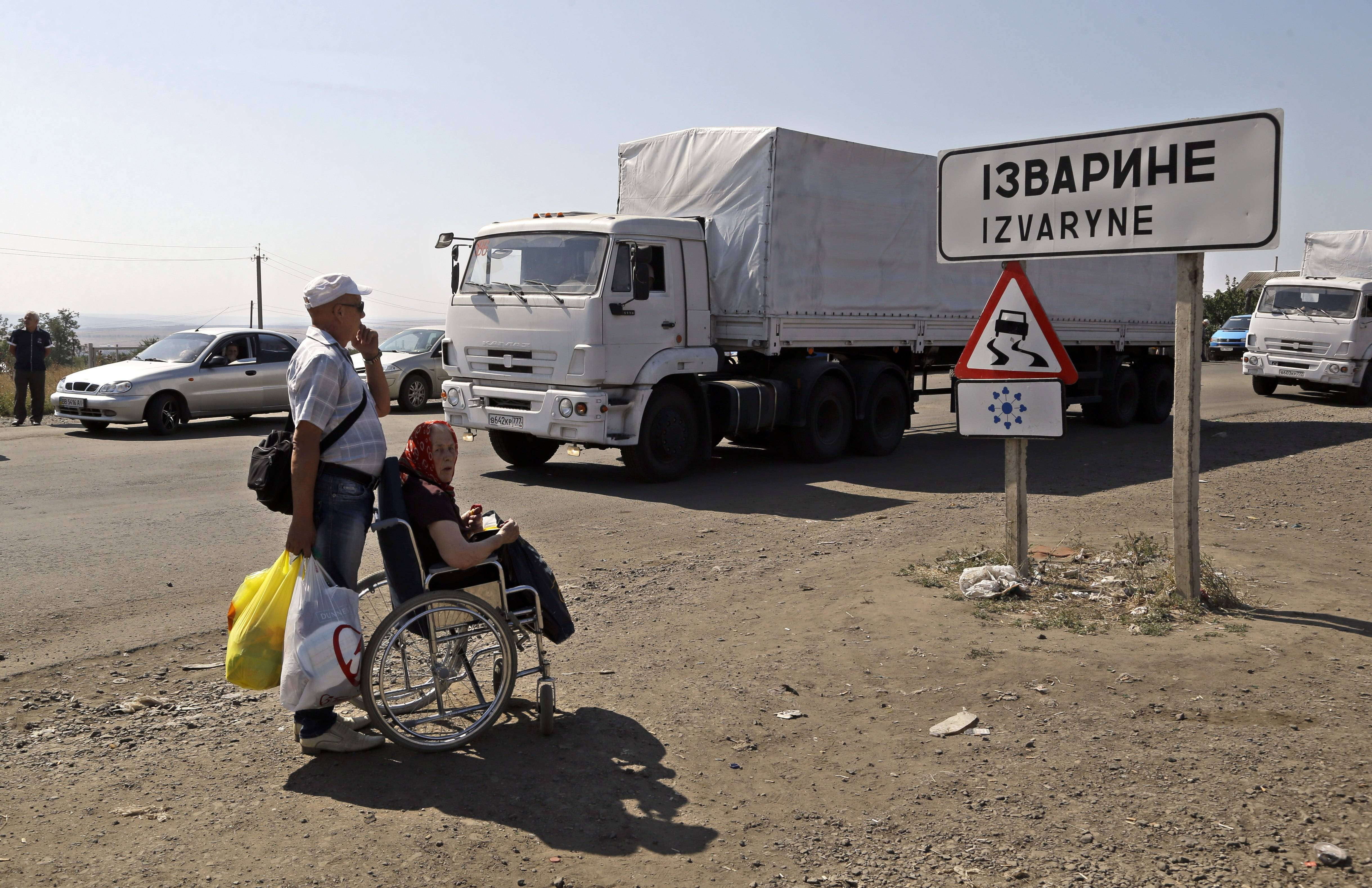 An elderly man and woman look at trucks, marked as being from a bitterly disputed Russian aid convoy to Ukraine, as they return Saturday to Russia on the border post at Izvaryne, eastern Ukraine.
