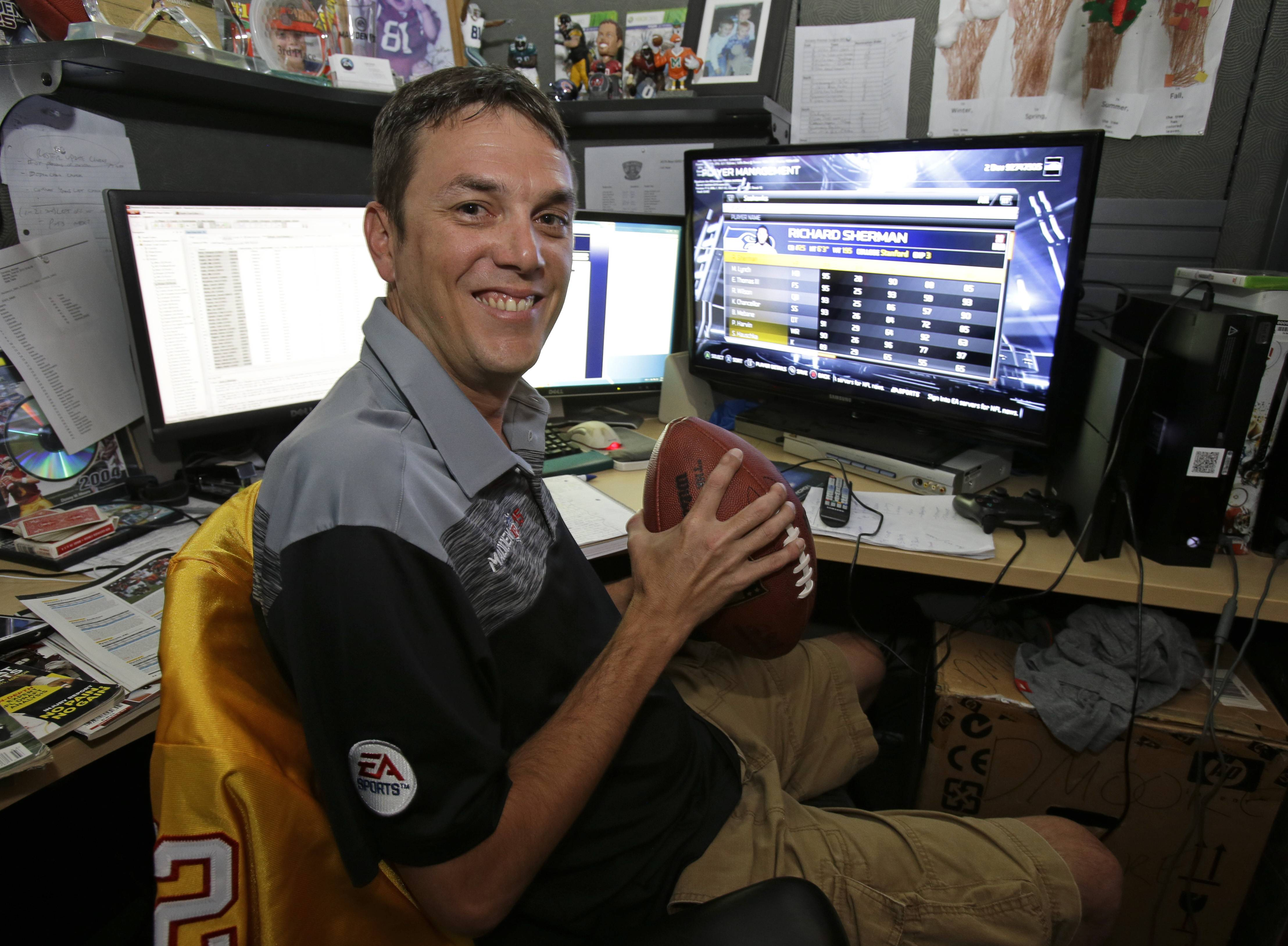 "Donny Moore poses for a photo in front three computer screens he uses to rate NFL football players for the Madden NFL video football game at EA Sports in Orlando, Fla. Moore is the ""ratings czar"" for ""Madden NFL,"" the man responsible for making sure the popular video game's virtual avatars accurately reflect their real-life counterparts."
