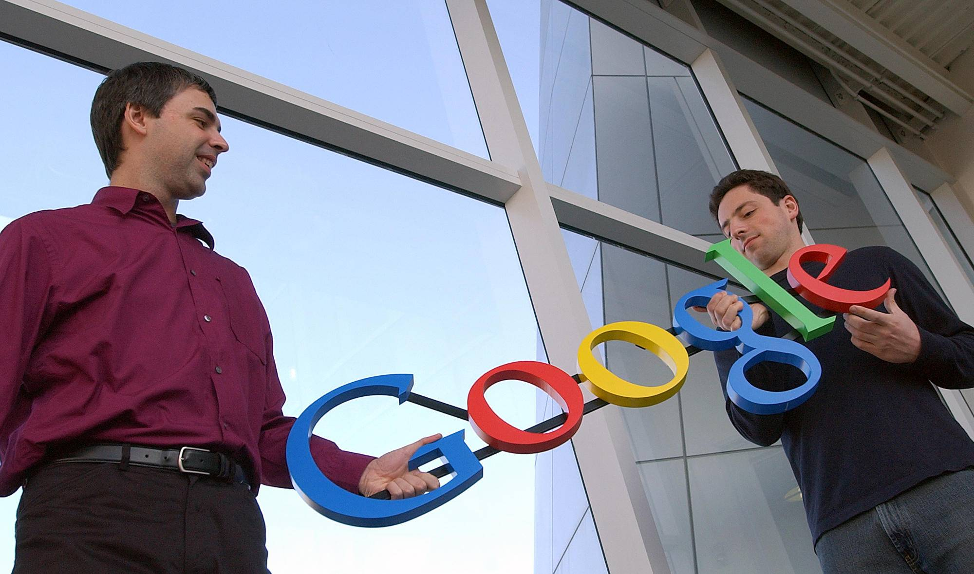 Google co-founders Larry Page, left, and Sergey Brin pose for photos at their company's headquarters in Mountain View, Calif. Google