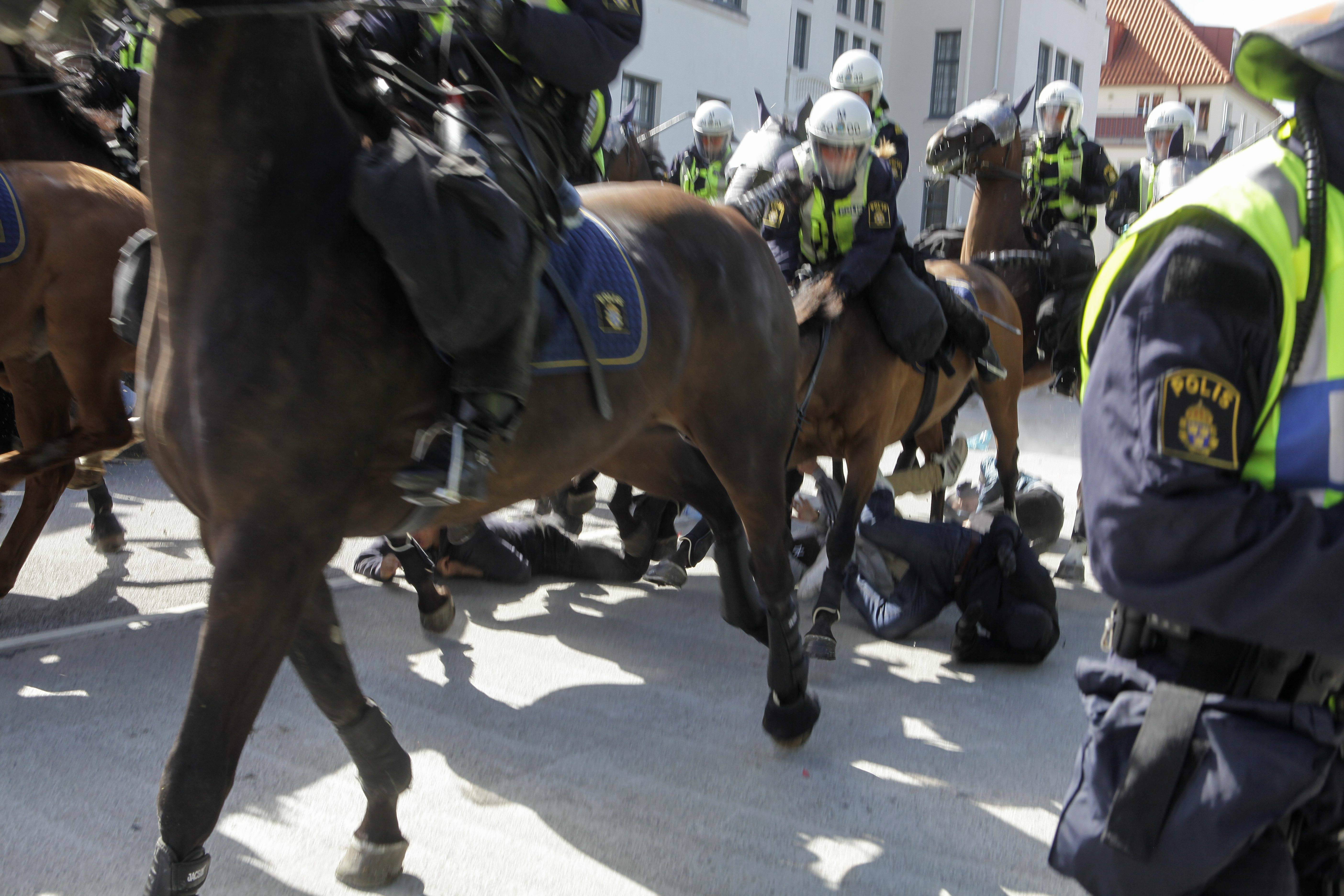 "Police mounted on horses ride Saturday through counter-demonstrators protesting against an election meeting arranged by the neo-nazi party ""Svenskarnas Parti"", at a square in central Malmo, Sweden."