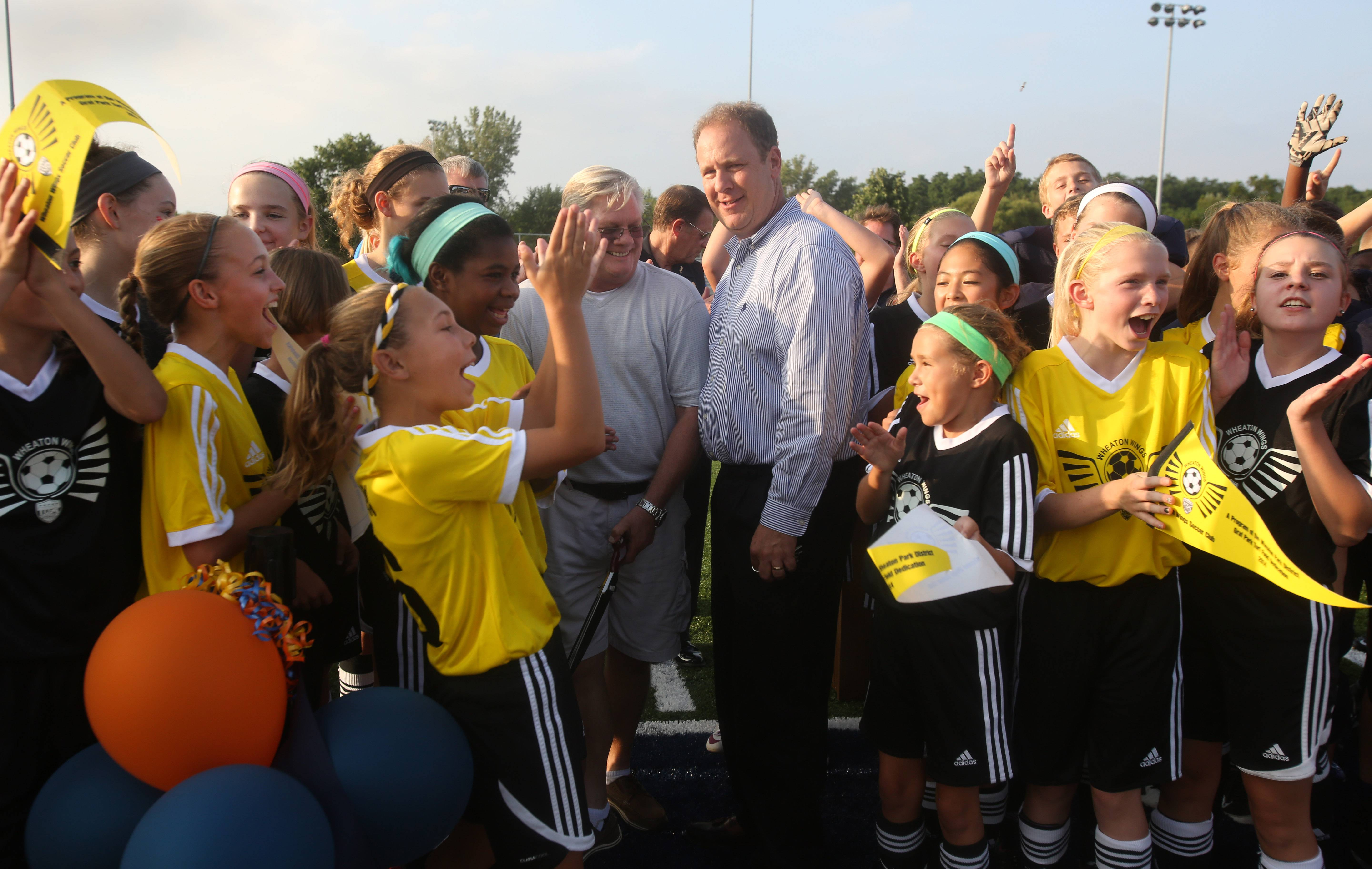 Wheaton Park District Commissioner Ray Morrill and Bill Farley assistant superintendent of Community Unit District 200, are cheered by Wheaton Wings youth soccer players after officially dedicating the installation of a new synthetic turf at Wheaton's Graf Park.