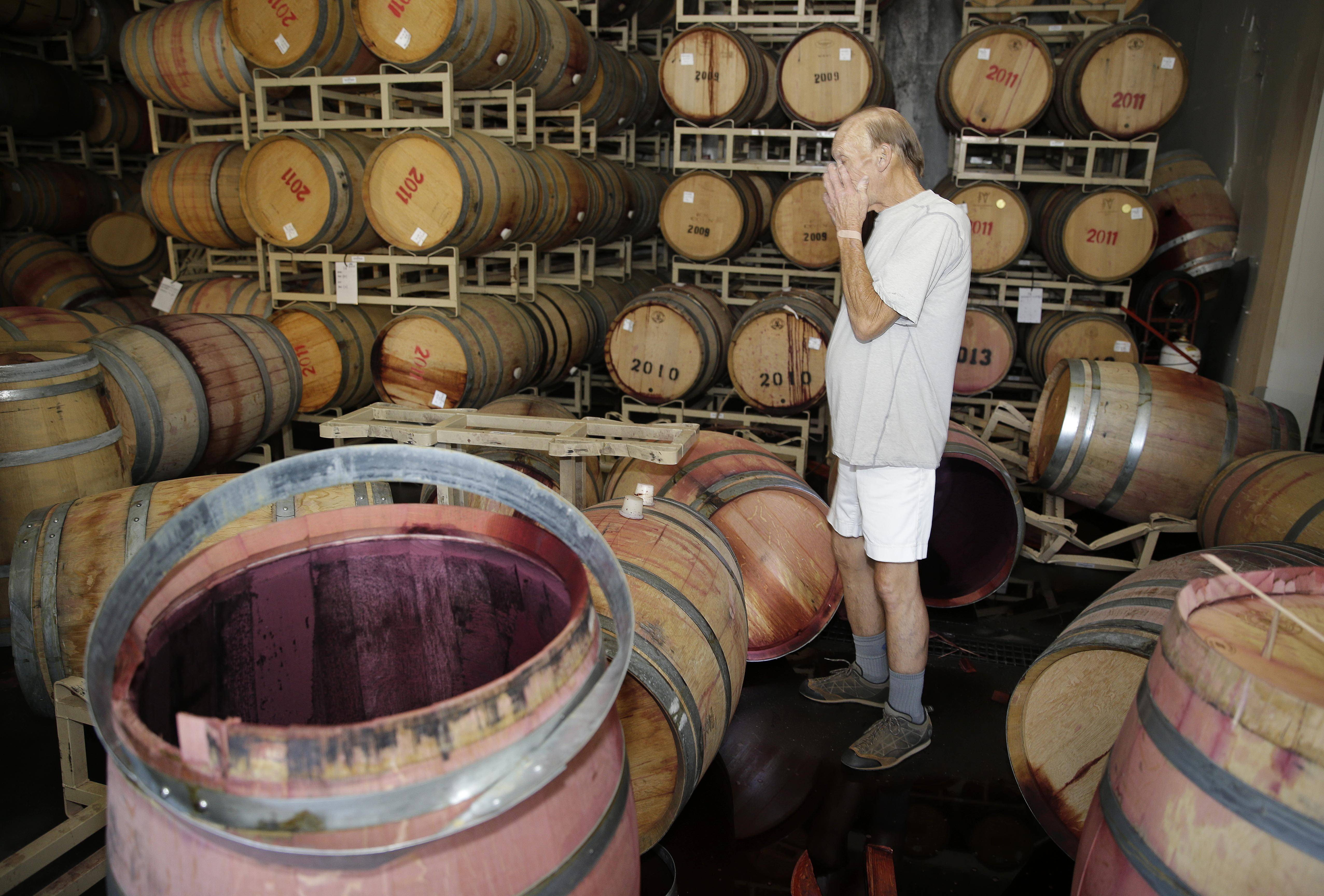 Winemaker Tom Montgomery reacts to seeing damage following an earthquake at the B.R. Cohn Winery barrel storage facility Sunday in Napa, Calif. Winemakers in California's storied Napa Valley woke up to thousands of broken bottles, barrels and gallons of ruined wine as a result of the earthquake.