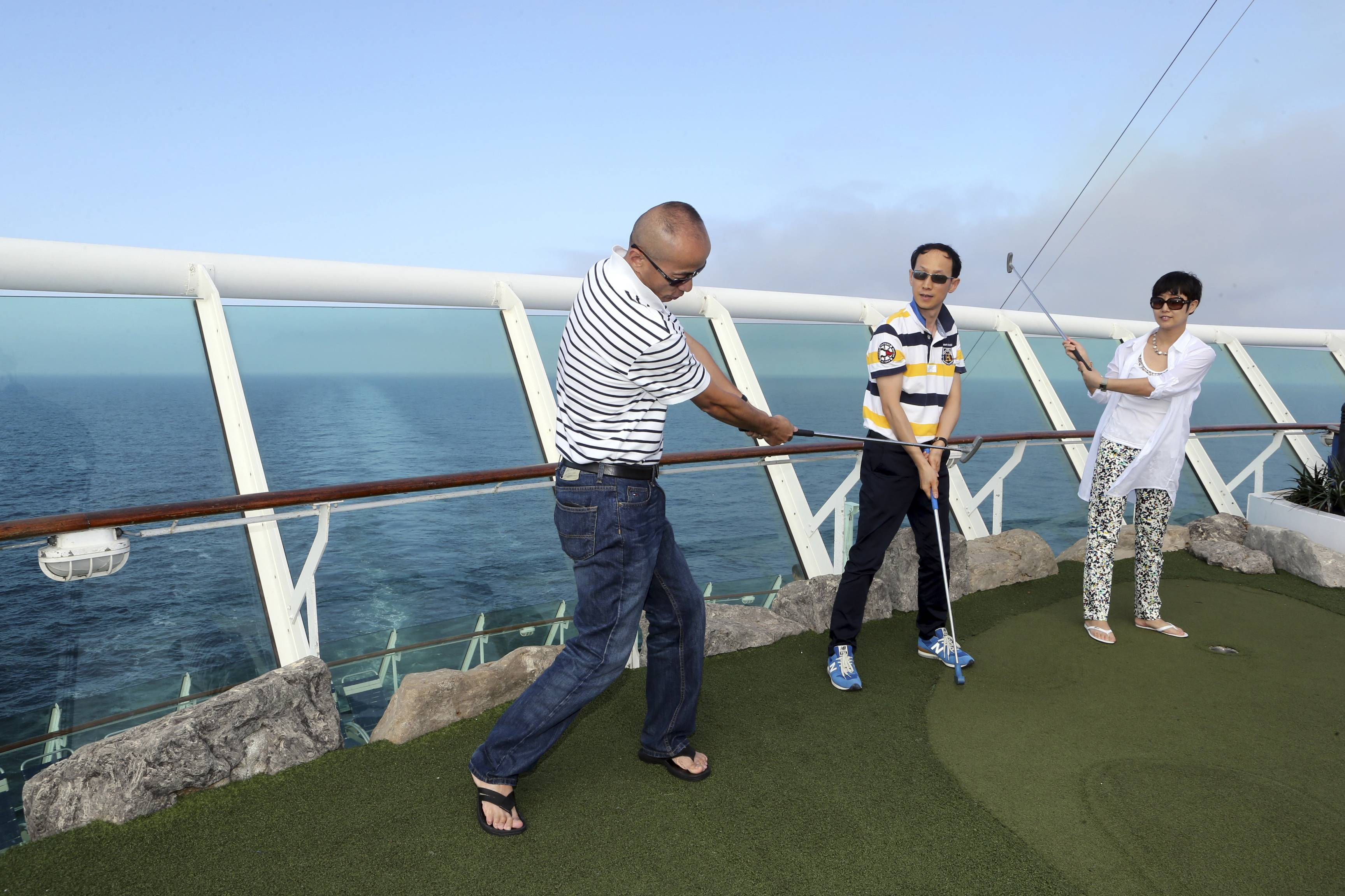 Chinese tourists play mini golf on the Royal Caribbean cruise ship Mariner of the Seas during her voyage from Shanghai, China, to Jeju, South Korea. The race for China underscores the growing strength of the leisure and travel industries in the world's No. 2 economy as authorities try to spur domestic spending rather than trade and investment as an engine of growth.