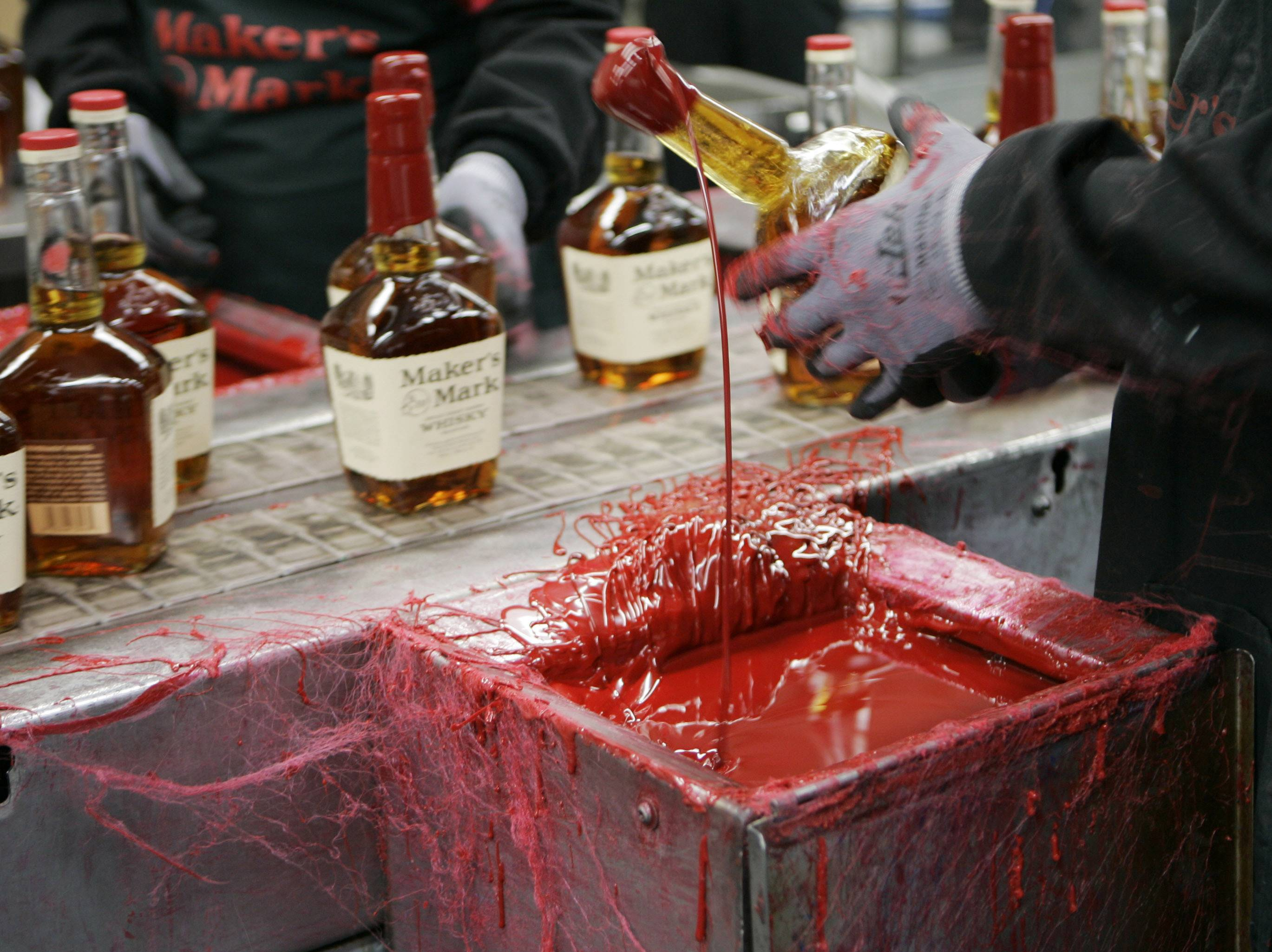 A bottle of Maker's Mark bourbon is dipped in red wax during a tour of the distillery in Loretto, Ky. Kentucky bourbon makers have stashed away their largest stockpiles in more than a generation due to resurgent demand for the venerable brown spirit.