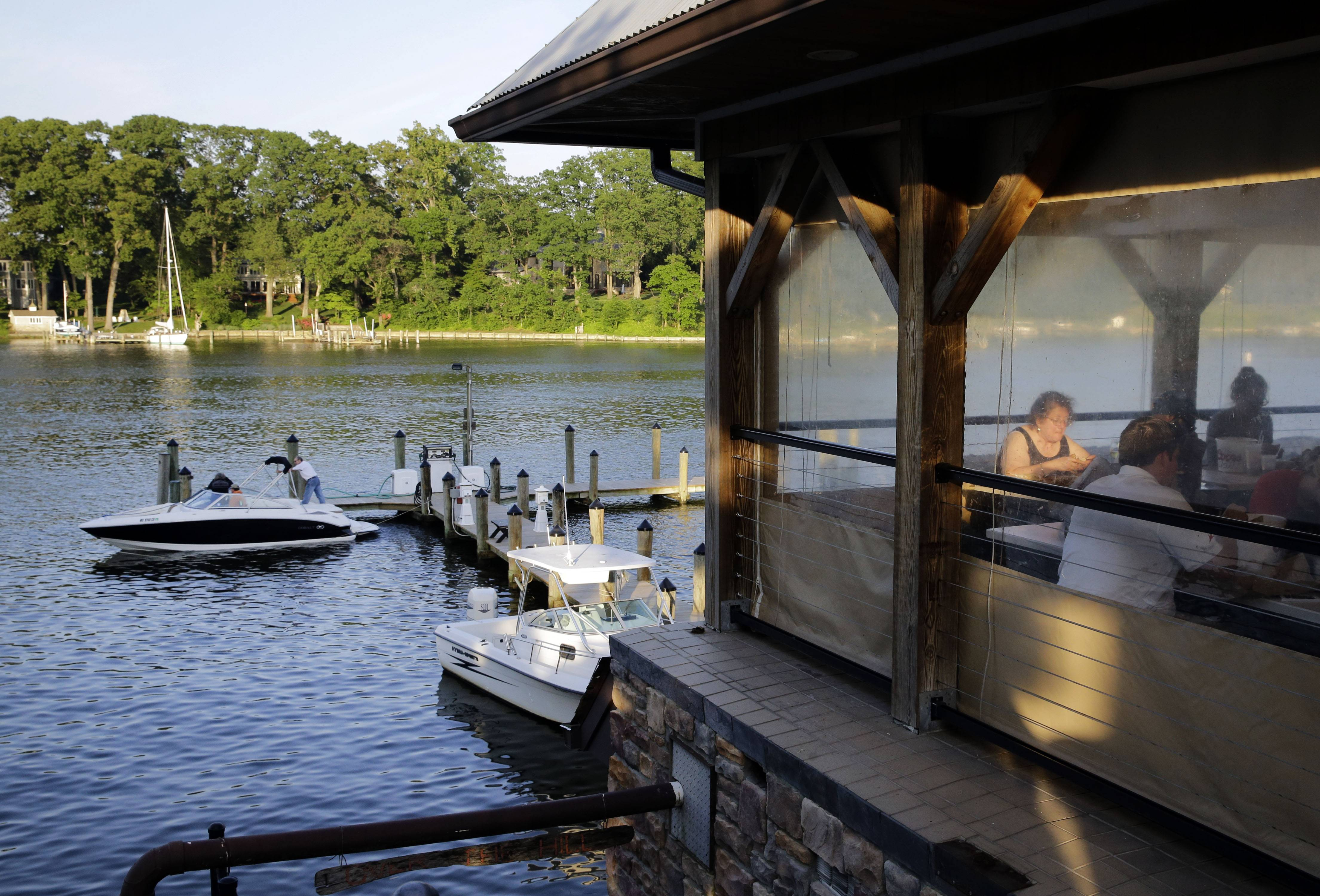 Patrons eat on the deck at Jimmy Cantler's Riverside Inn as diners prepare to untie their boat from the restaurant's dock.