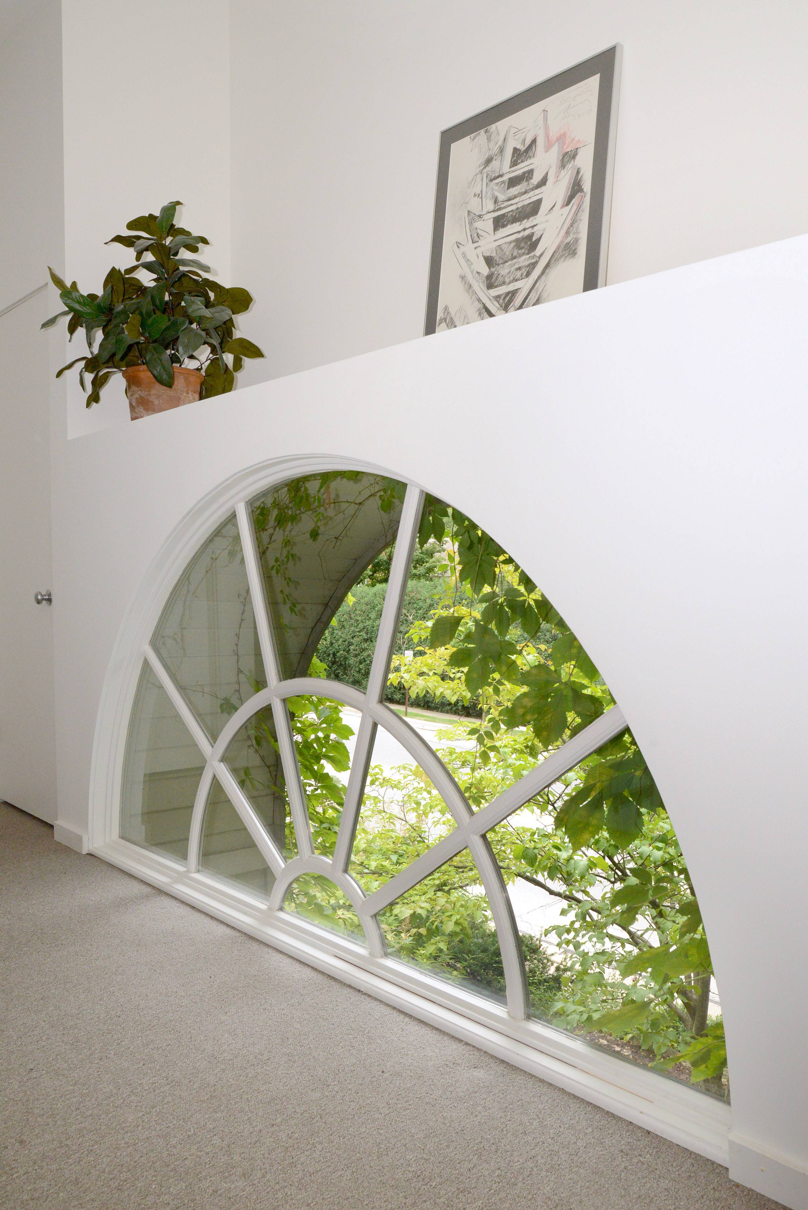 Arched window over the front door of the home as viewed from inside on the second floor.