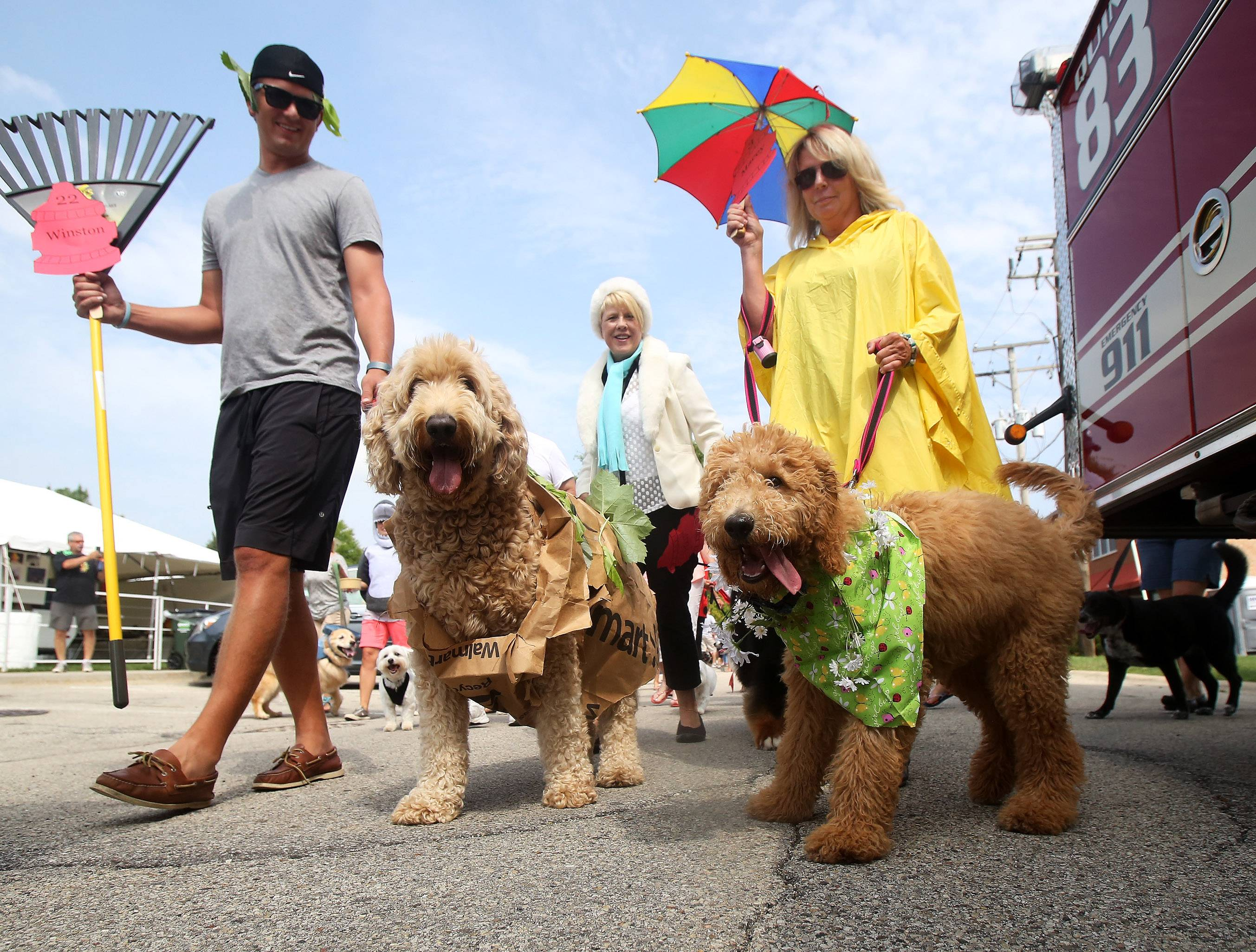 Dressed as the four seasons, Brad Rathe of Deer Park, left, walks with Winston, and Cheryl Rathe marches with Macey, during the annual Sweet Pea Pet Parade in downtown Palatine. More than 70 pets participated in the parade Sunday dressed in costumes ranging from sports figures to food items.