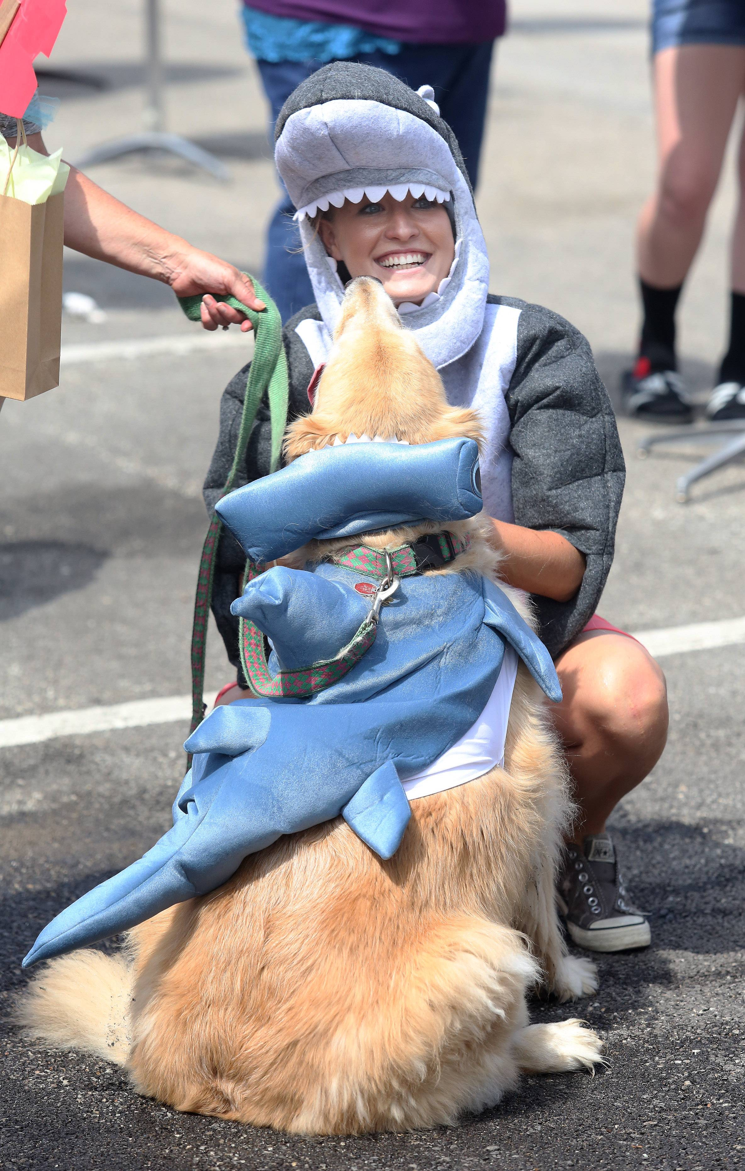 Heather Glaser of Palatine hugs Nellie as they dress as a pair of sharks during the annual Sweet Pea Pet Parade Sunday in downtown Palatine. More than 70 pets participated in the parade Sunday dressed in costumes ranging from sports figures to food items.