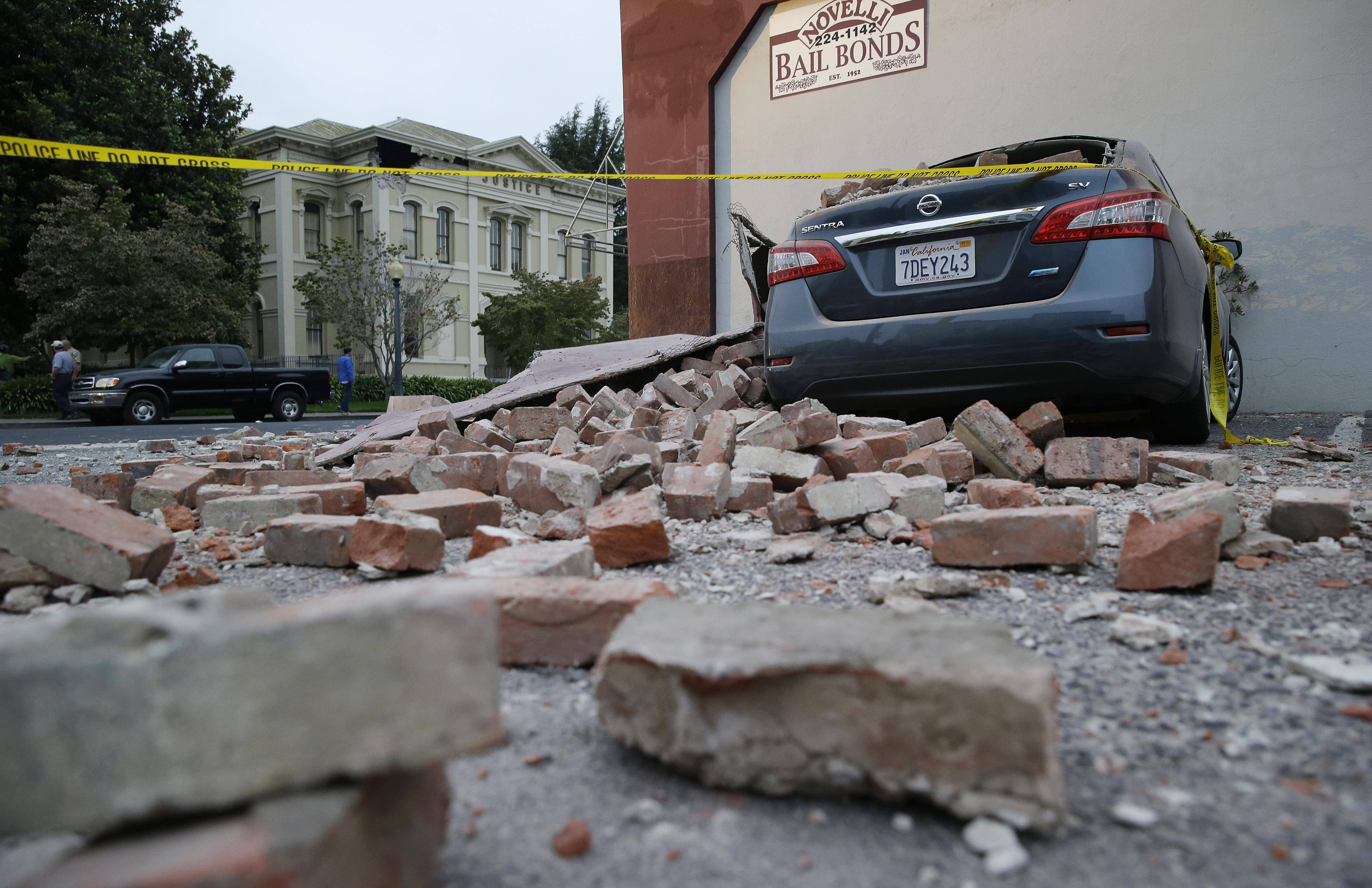 Bricks are in the street after a building was damaged during an earthquake in Napa, Calif., Sunday. A large earthquake rolled through California's northern Bay Area early Sunday, damaging some buildings, knocking out power to thousands and sending residents running out of their homes in the darkness.