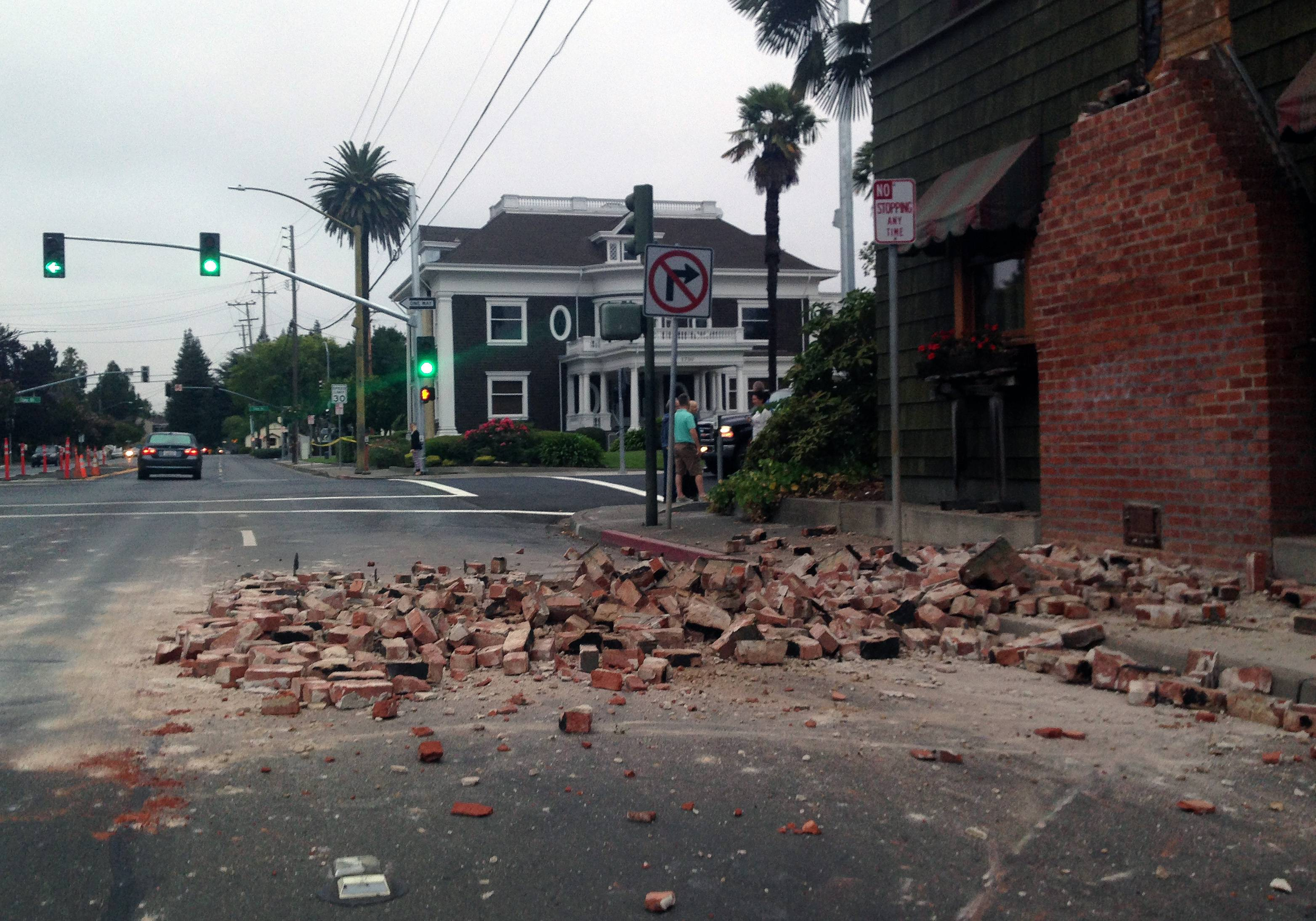 People walk past a tumbled mannequin and broken storefront window on First Street following an earthquake Sunday in Napa, Calif. A large earthquake rolled through California's northern Bay Area early Sunday, damaging some buildings, igniting fires, knocking out power to tens of thousands and sending residents running out of their homes in the darkness.