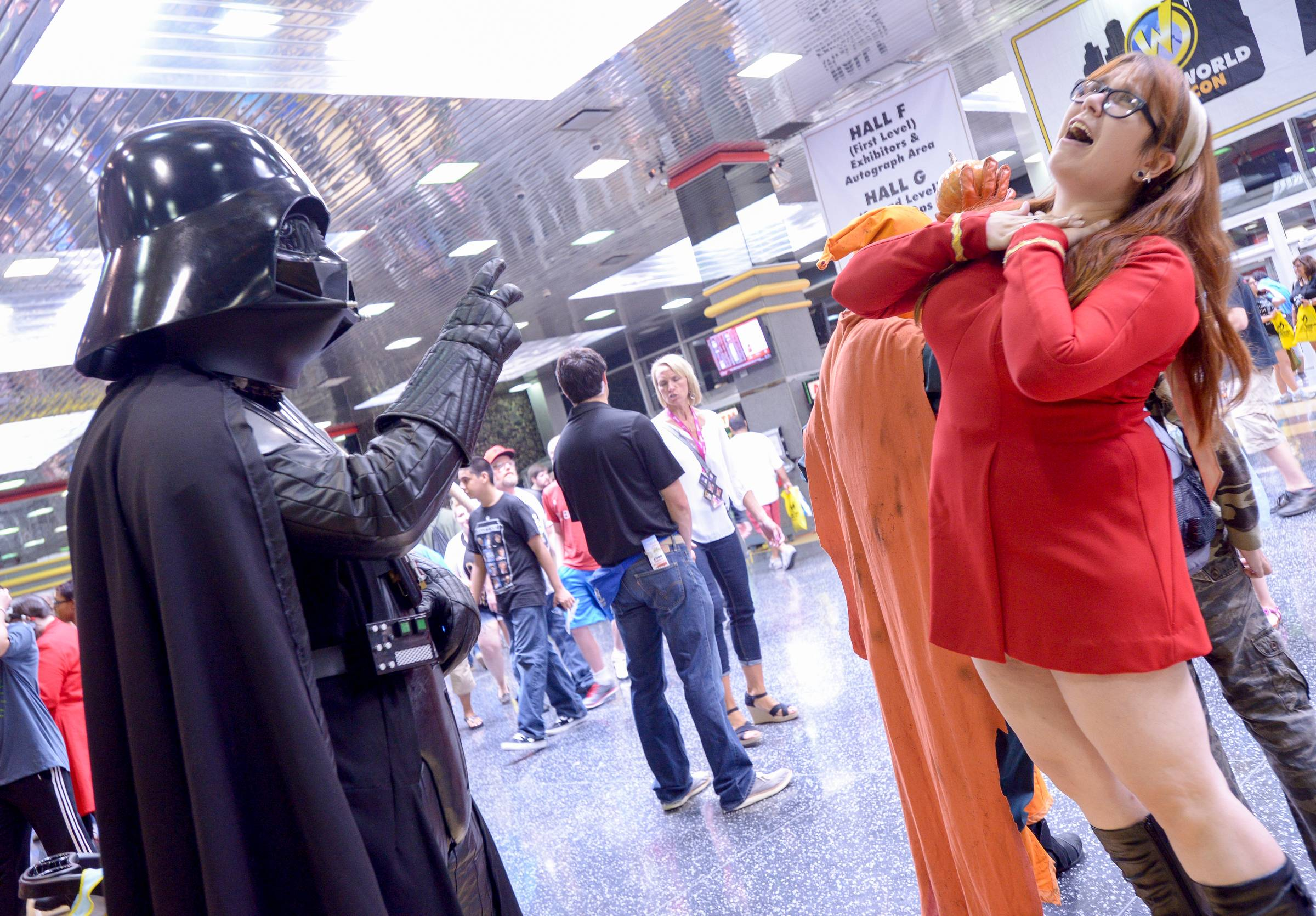 "Darth Vader from the Star Wars series uses the dark force to ""choke"" Megan Morgan of Schaumburg dressed as a ""Red Shirt"" from the original Star Trek TV series during the Comic Con convention at the Donald E. Stephens Convention Center in Rosemont."