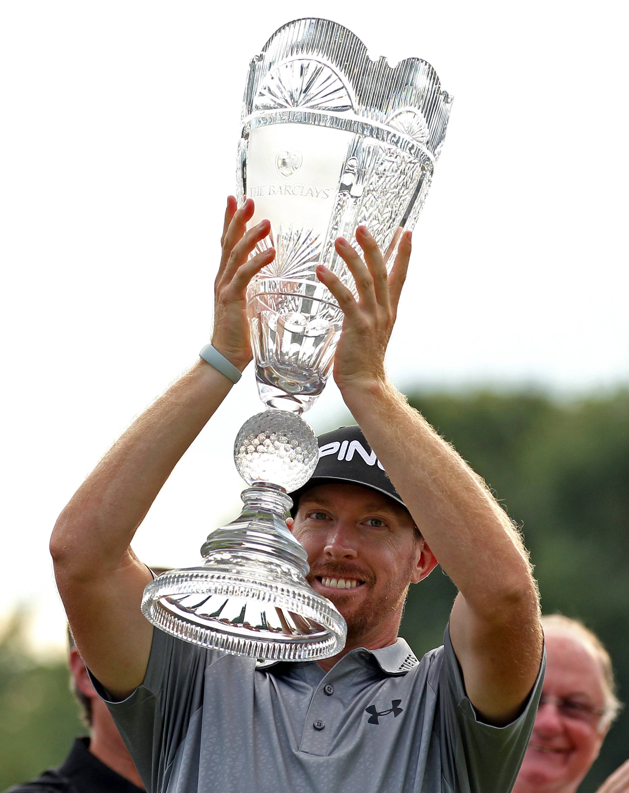Hunter Mahan holds up the trophy after winning at The Barclays golf tournament Sunday in Paramus, N.J. Mahan won the tournament with a 14 under-par 270.
