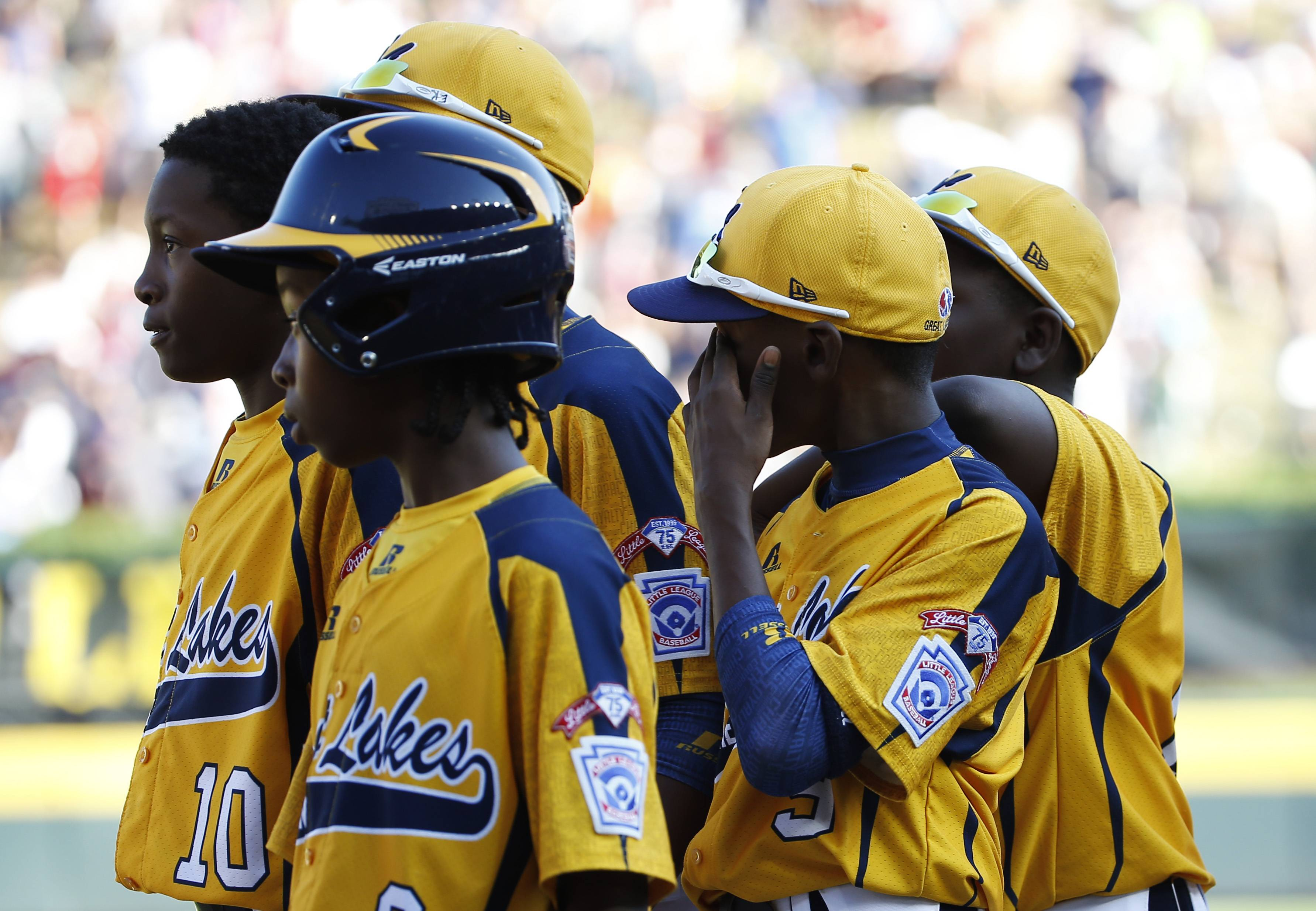 Jackie Robinson West players watch as South Korea players celebrate after winning the championship baseball game at the Little League World Series, Sunday, in South Williamsport, Pa. South Korea won 8-4.