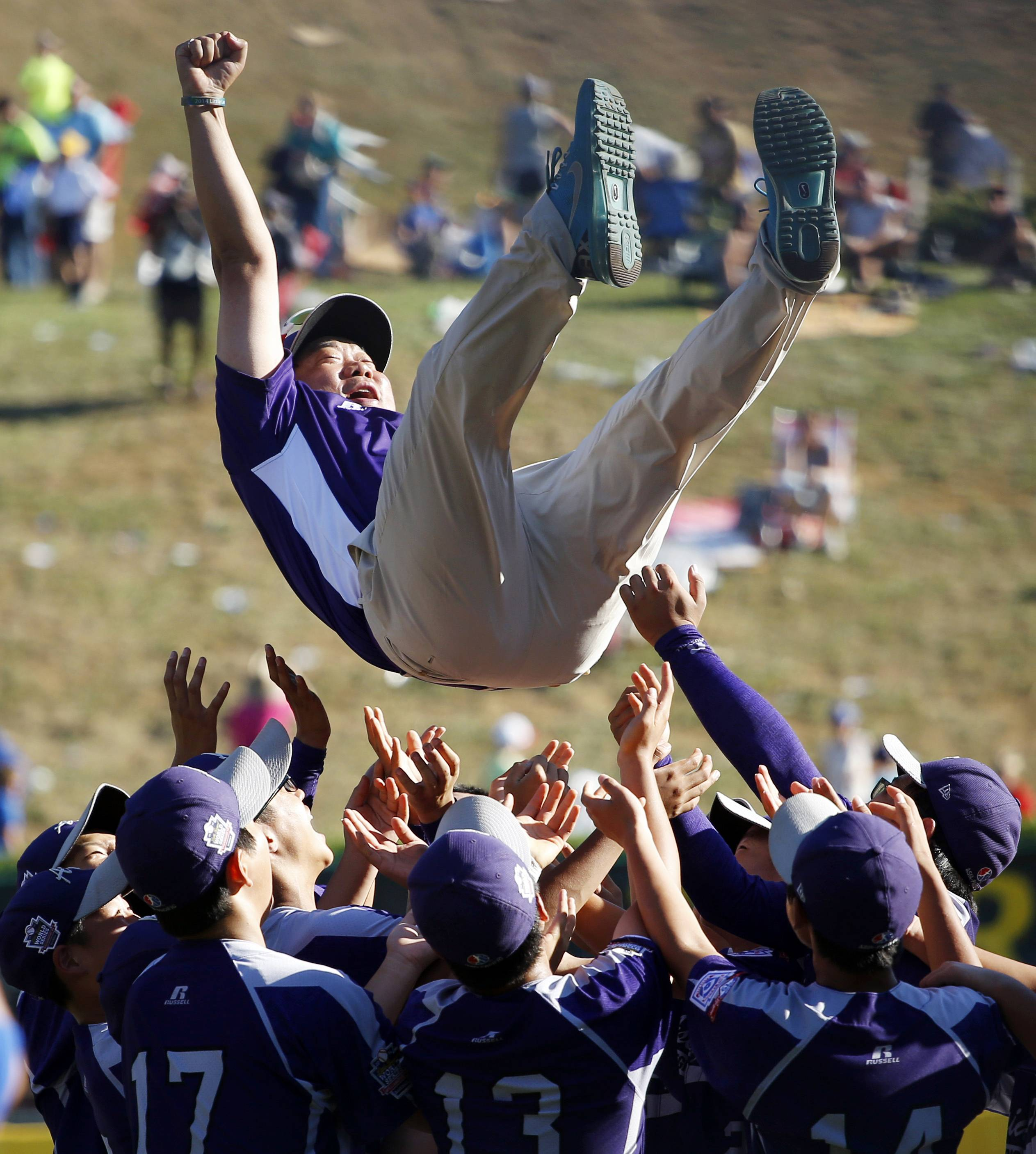 South Korea players toss their coach into the air after winning the championship baseball game against Chicago at the Little League World Series, Sunday.