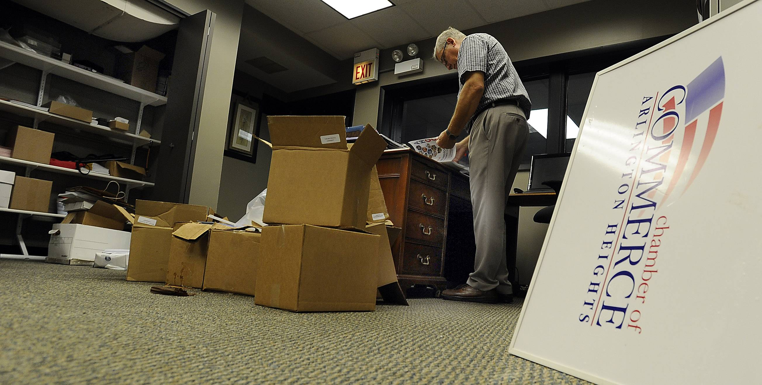 Employees of the Arlington Heights Chamber of Commerce go about their work Monday, around the water-soaked boxes of materials. The office got about 4 inches of water over the weekend — the second time their office has been flooded.