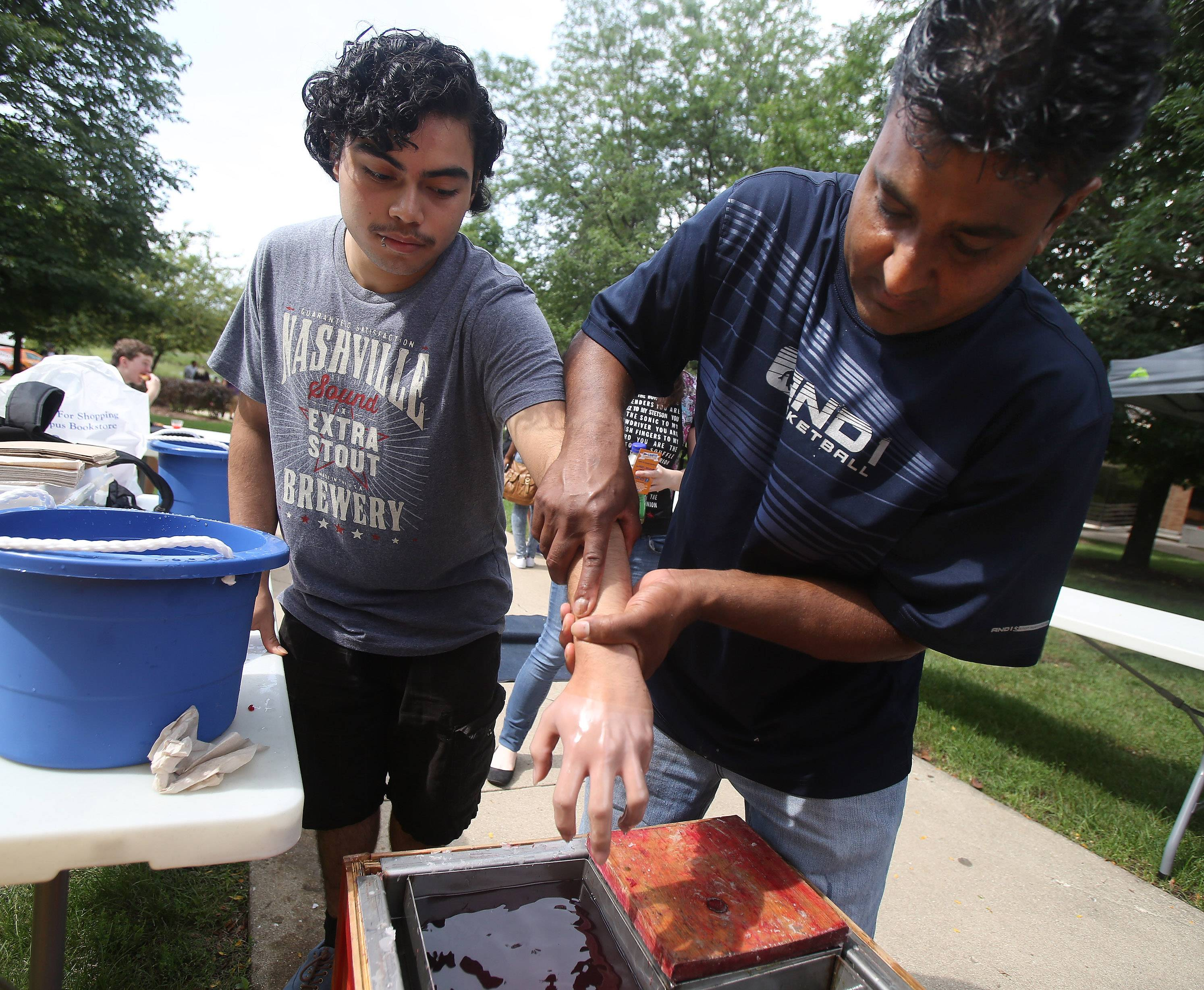 Joel Munoz of Waukegan, left, has a wax hand mold made by Gershom Rangai of Leaping Lizards Entertainment on Monday, the first day of classes at the College of Lake County. CLC Student Activities offered free pizza, popcorn, sandwiches and soda pop, as well as a climbing wall and free wax hands.