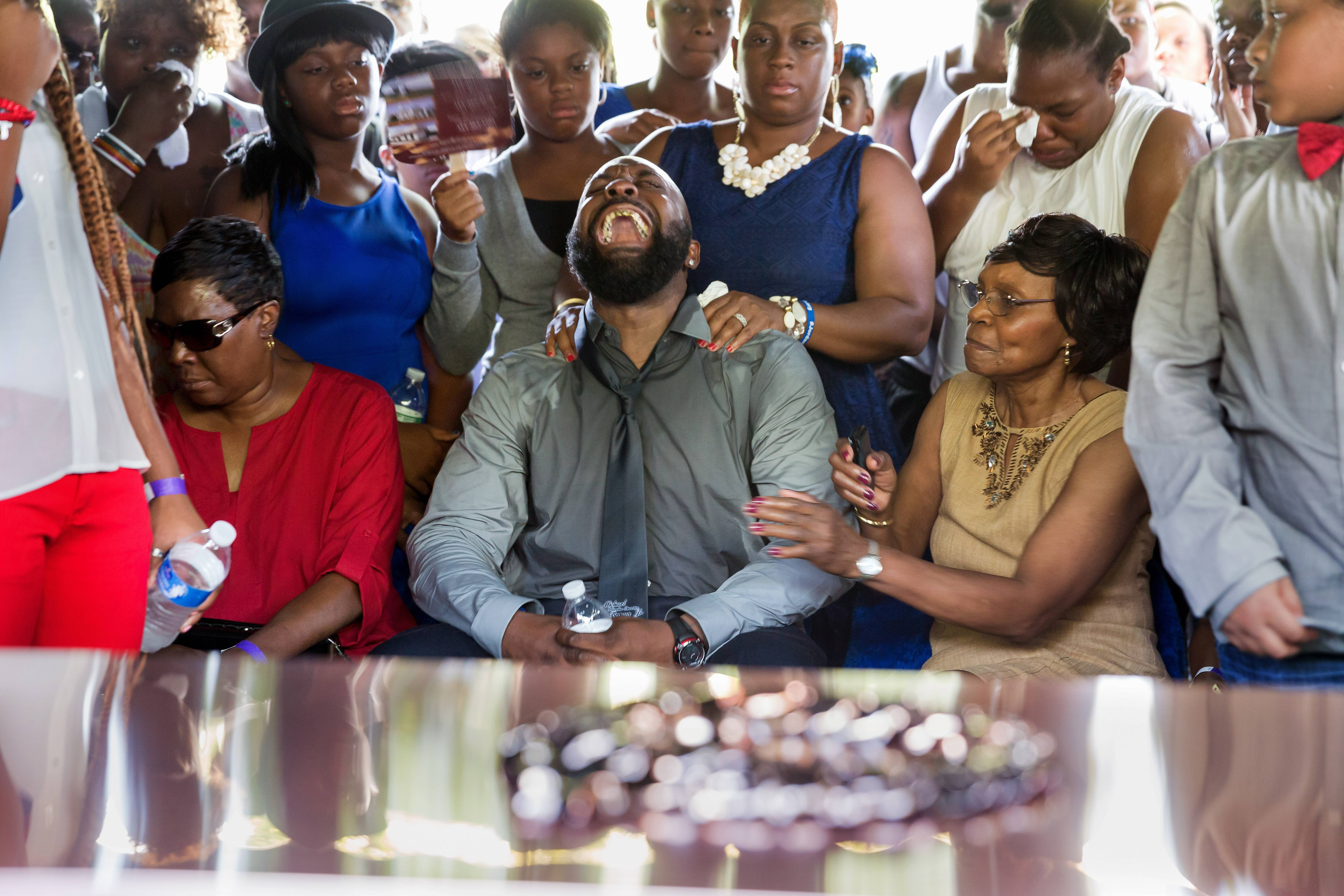 Michael Brown Sr. yells out as the casket is lowered during the funeral service for his son Michael Brown in Normandy, Mo.
