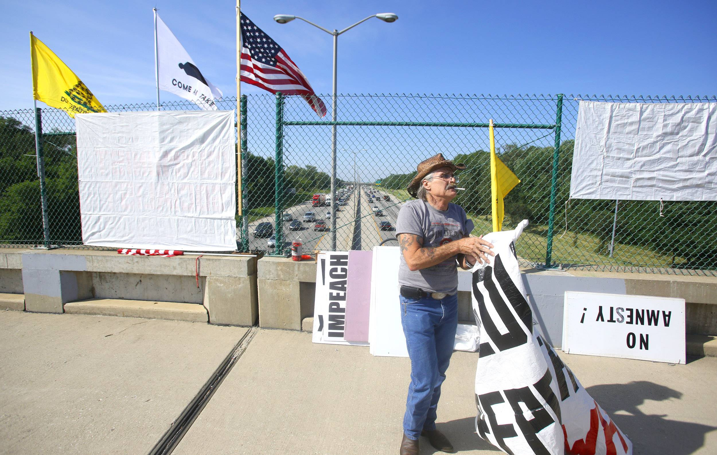 Mike Malone of the Overpasses for America group readies some protest signs on the Great Western Trail footbridge over I-355.