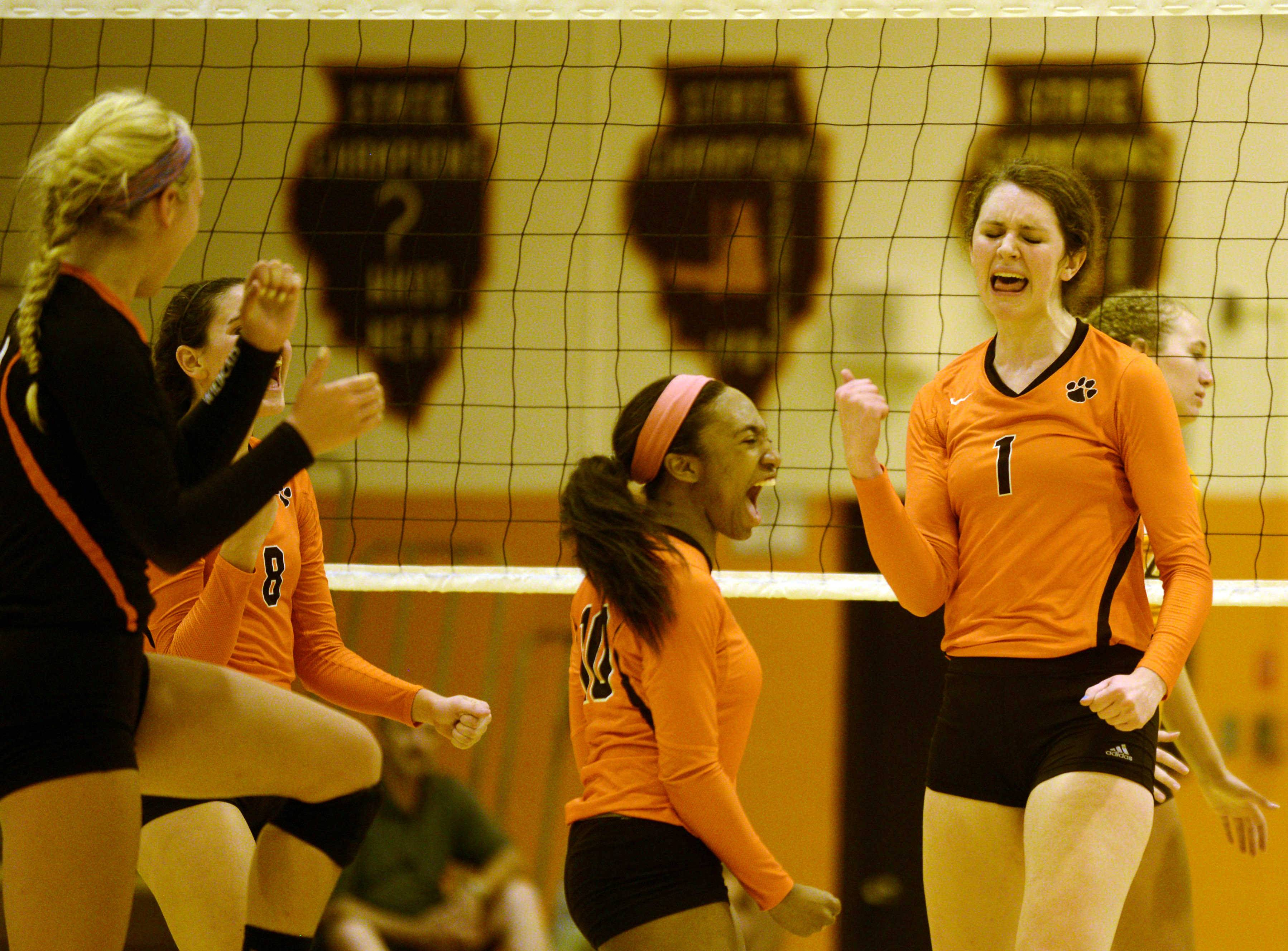 Libertyville's Eryka Jones, center, and Alex Basler, right, lead cheers during the Wildcats' victory Monday at Hersey.