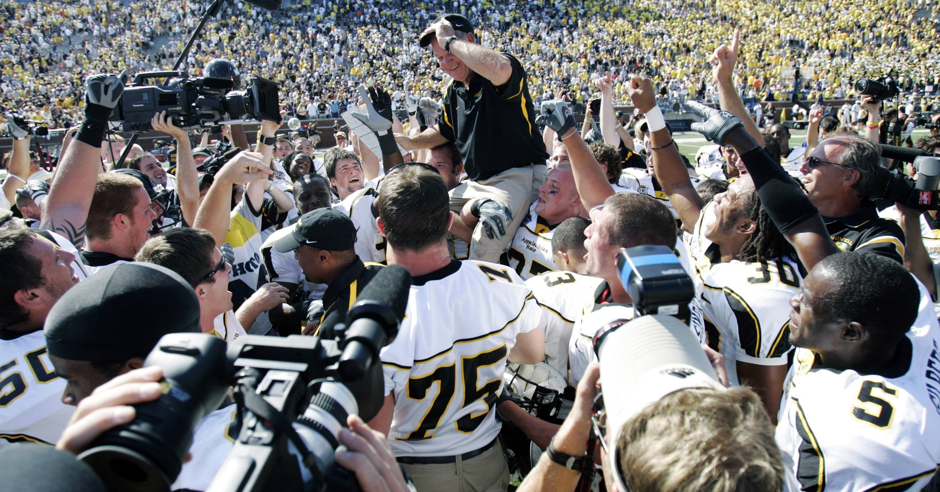 Appalachian State players carry coach Jerry Moore off the field after they upset No. 5 Michigan 34-32 in Ann Arbor.