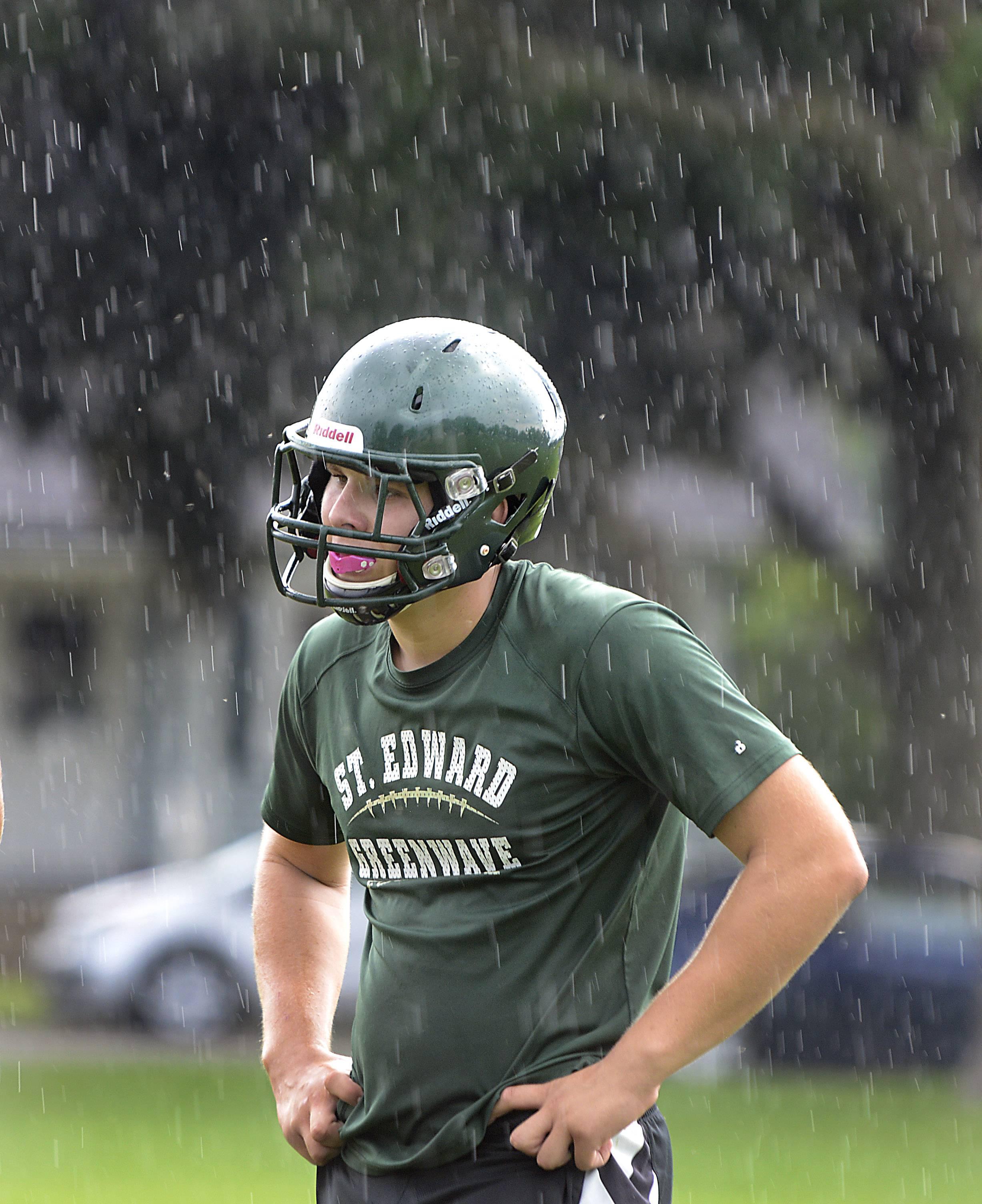 Brandon Ostrander stands in the cooling rain during a St. Edward practice.