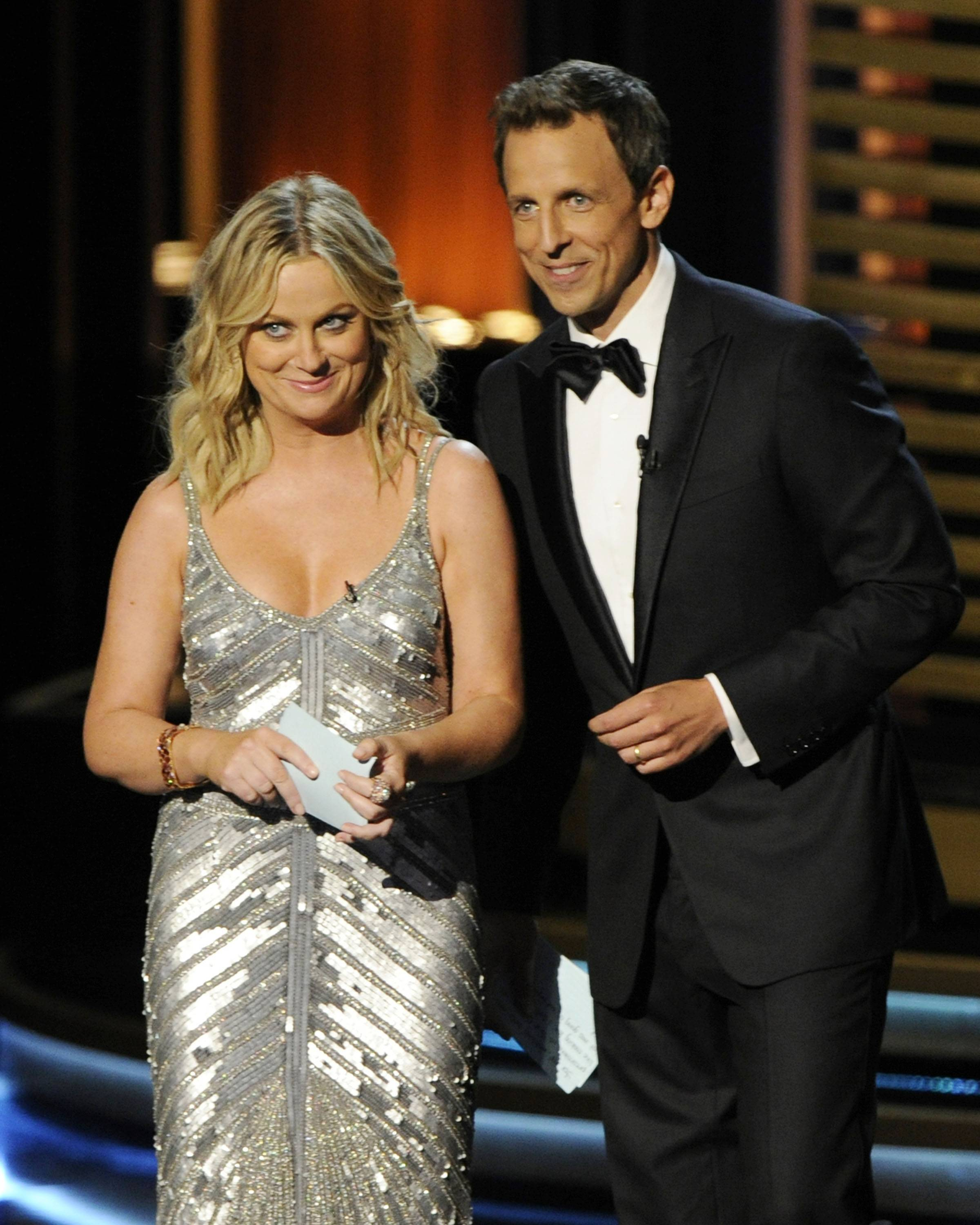 Amy Poehler, left, and host Seth Meyers speak onstage.