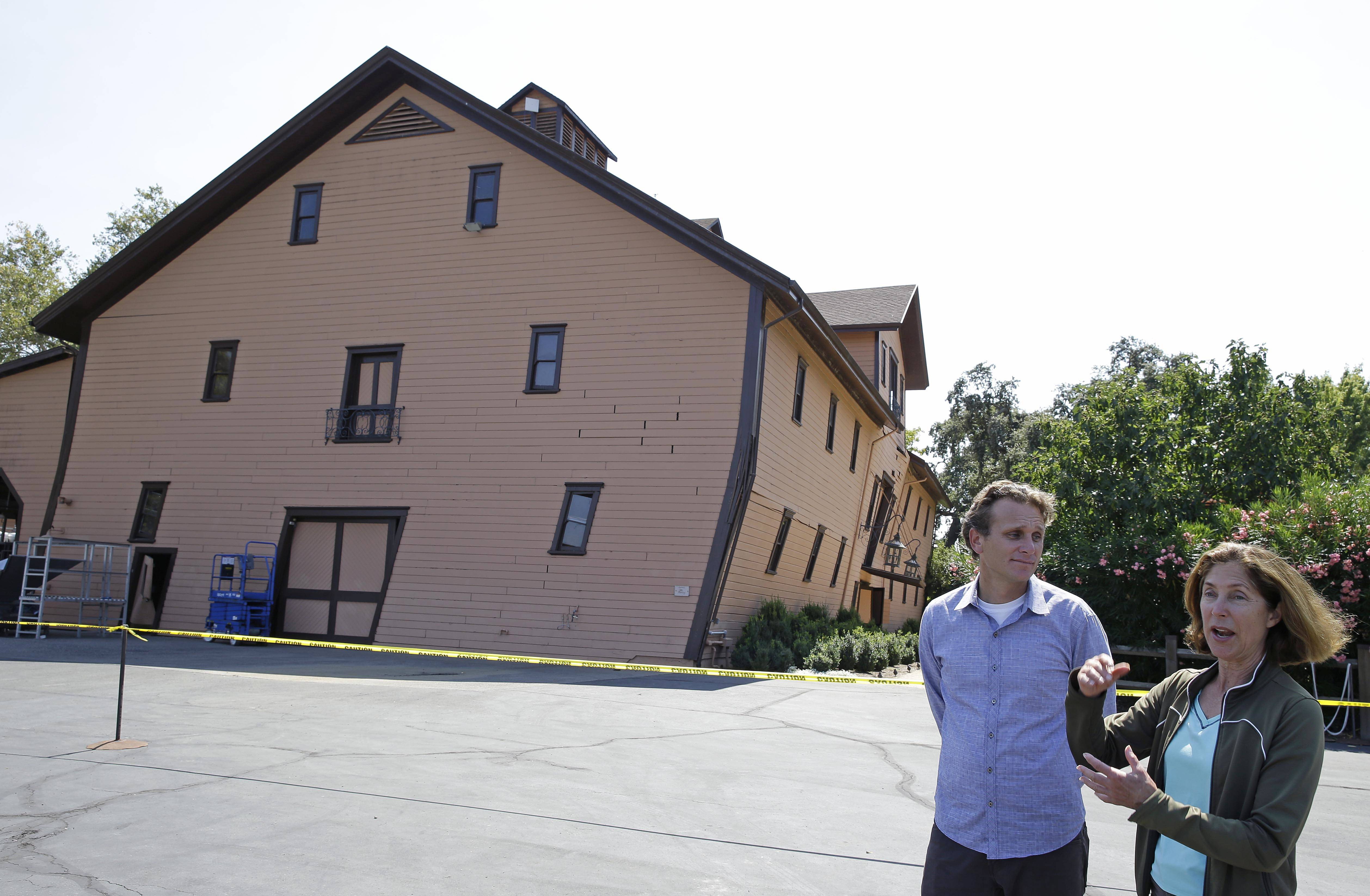 Owner Janet Trefethen, right, and president Jon Ruel, left, talk about the earthquake damage to the historic winery building, seen in the background, dating from 1886 at Trefethen Family Vineyards Monday in Napa, Calif. The winery is hopeful they can save the building after San Francisco Bay Area's strongest earthquake in 25 years struck the heart of California's wine country early Sunday.