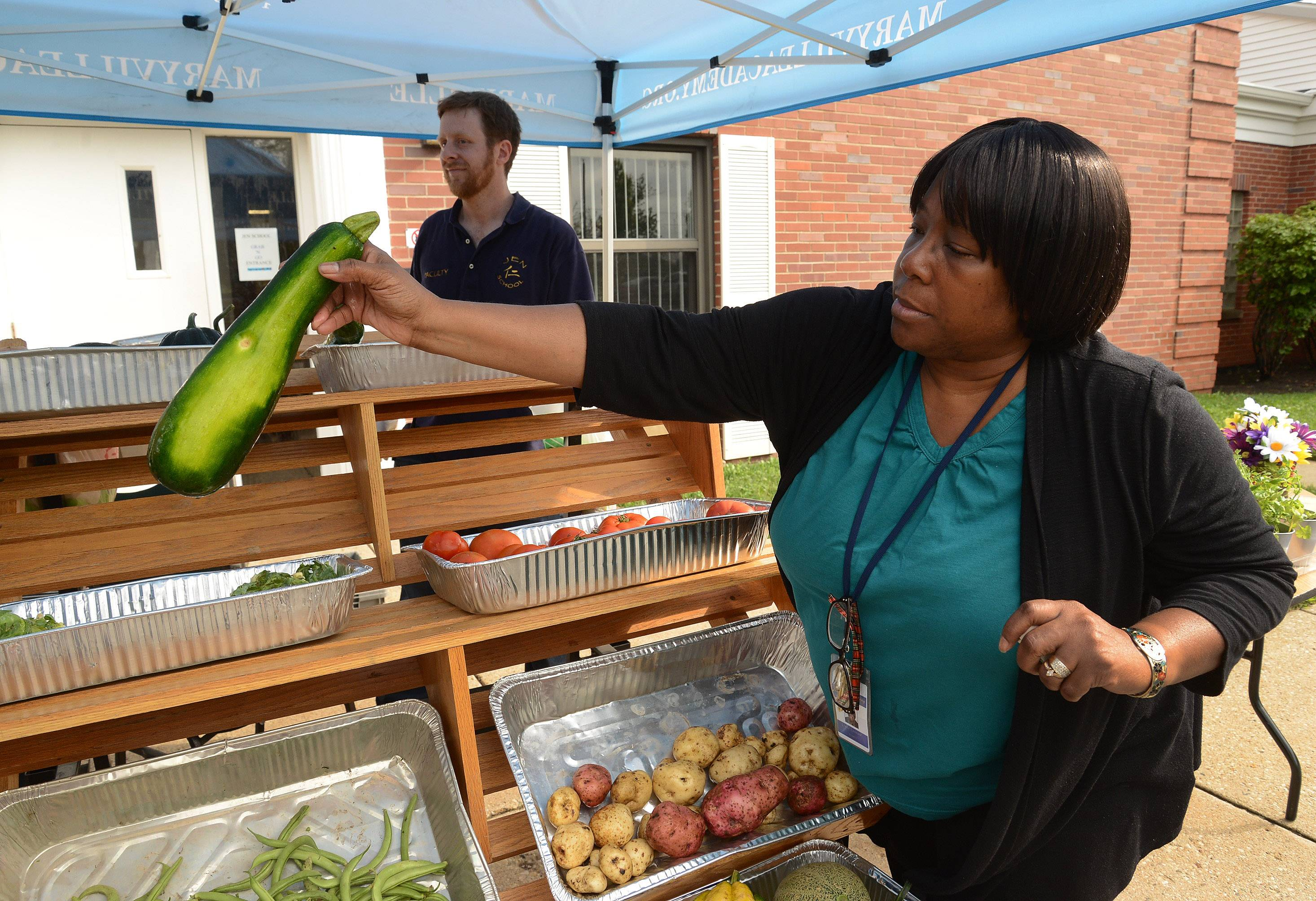 Maryville staff member Linda Leonard buys some zucchini from students selling their own homegrown produce at Maryville Academy.