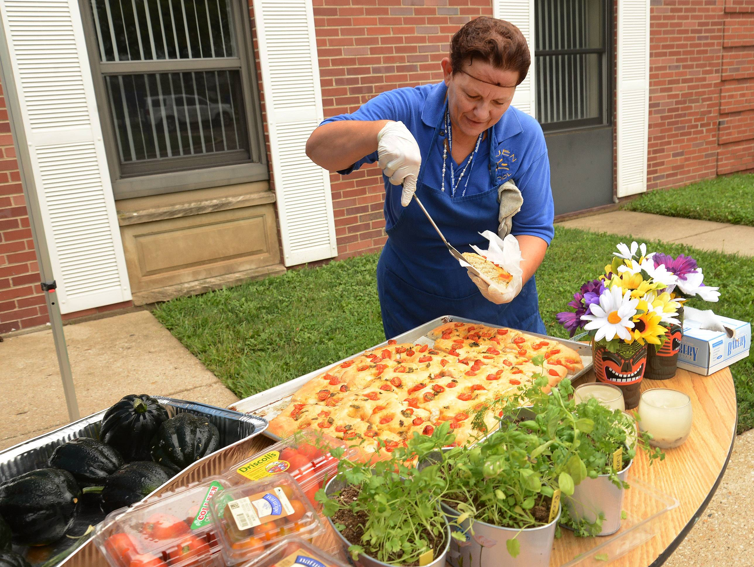 Chef Toni Tomasello slices up focaccia made with tomatoes and basil from students selling their own homegrown produce at Maryville Academy.