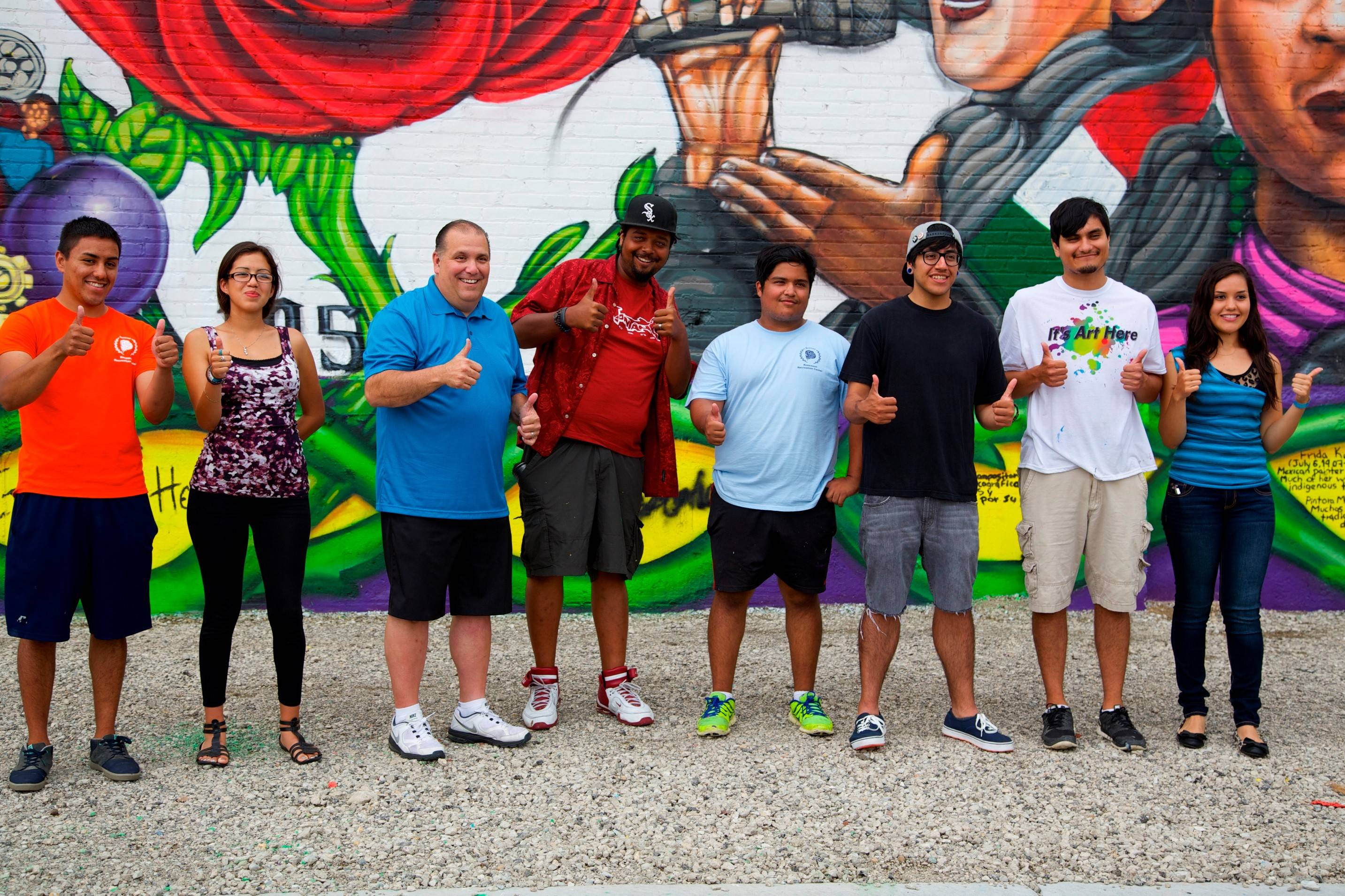 Rosemont Mayor Brad Stephens, third from left, and Chicago muralist Rahmaan Statik, fourth from left, joined local student artists on Saturday to unveil three murals they created near the Rosemont Recreation Center. The murals depict images of Mexican history and culture.