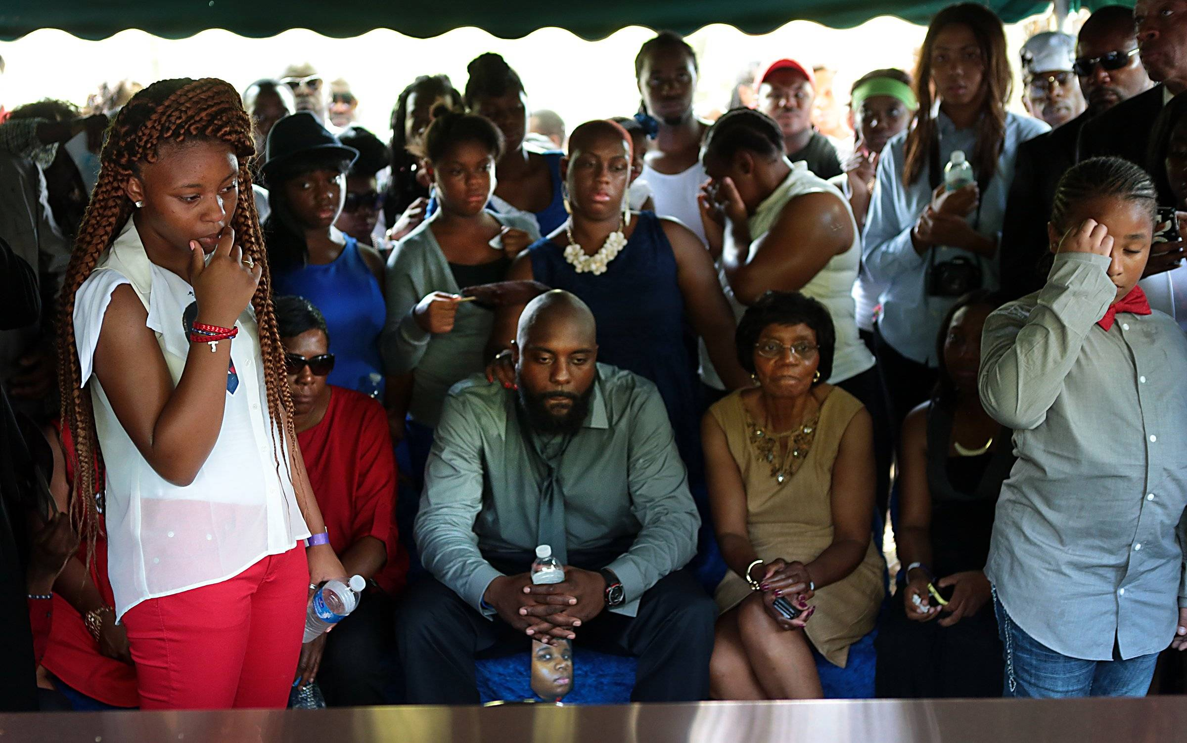 The family of Michael Brown, including his father Michael Brown Sr., center, watches as his vault is lowered during the funeral for Michael Brown on Monday in Normandy, Mo.