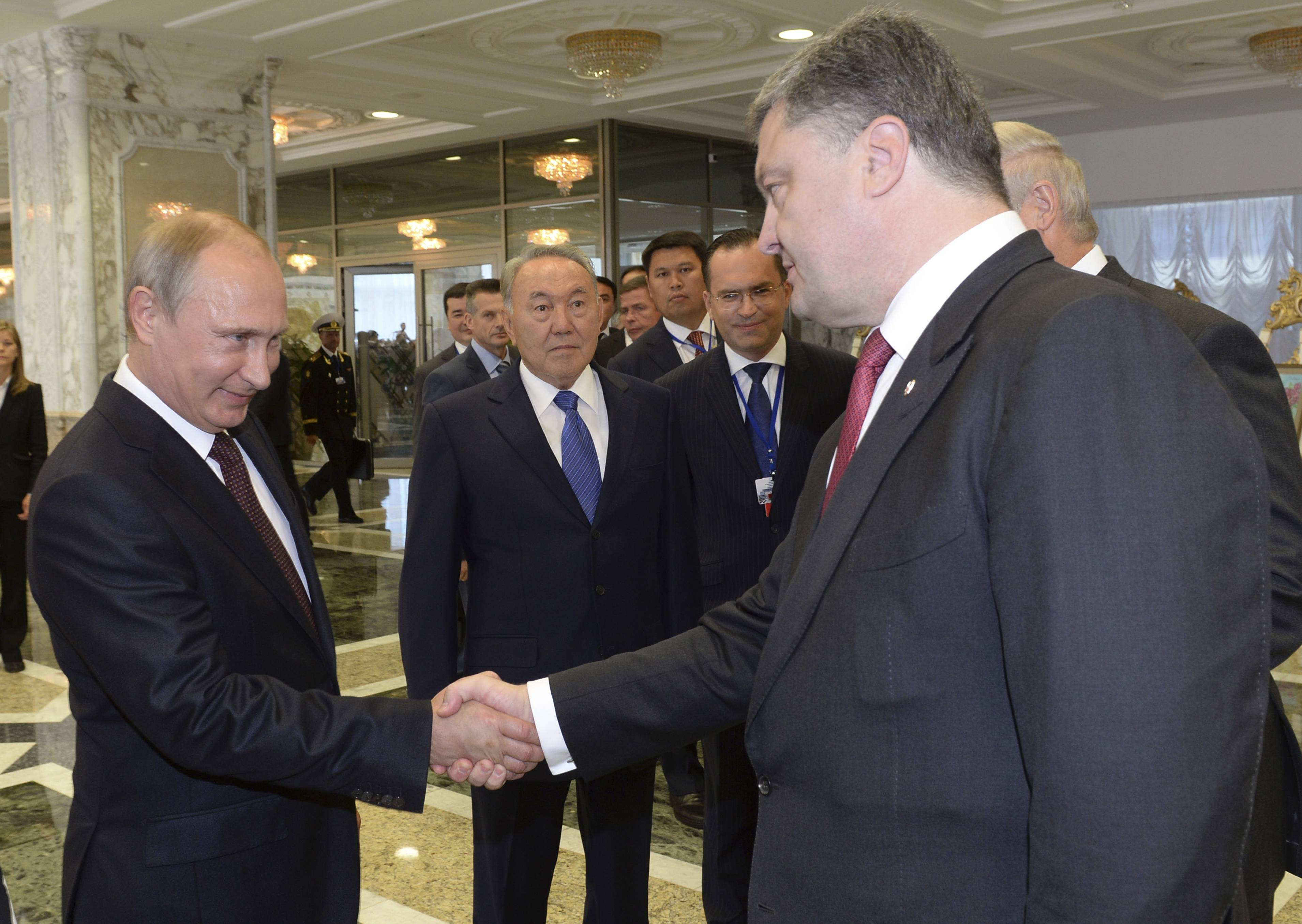Russian President Vladimir Putin, left, shakes hands with Ukrainian President Petro Poroshenko, right, as Kazakh President Nursultan Nazarbayev, center, looks on. Leaders of Russia, Belarus, two other former Soviet republics as well as top EU officials are meeting in Minsk, Belarus, for a highly anticipated summit to discuss the crisis in Ukraine which has left more than 2,000 dead and displaced over 300,000 people.