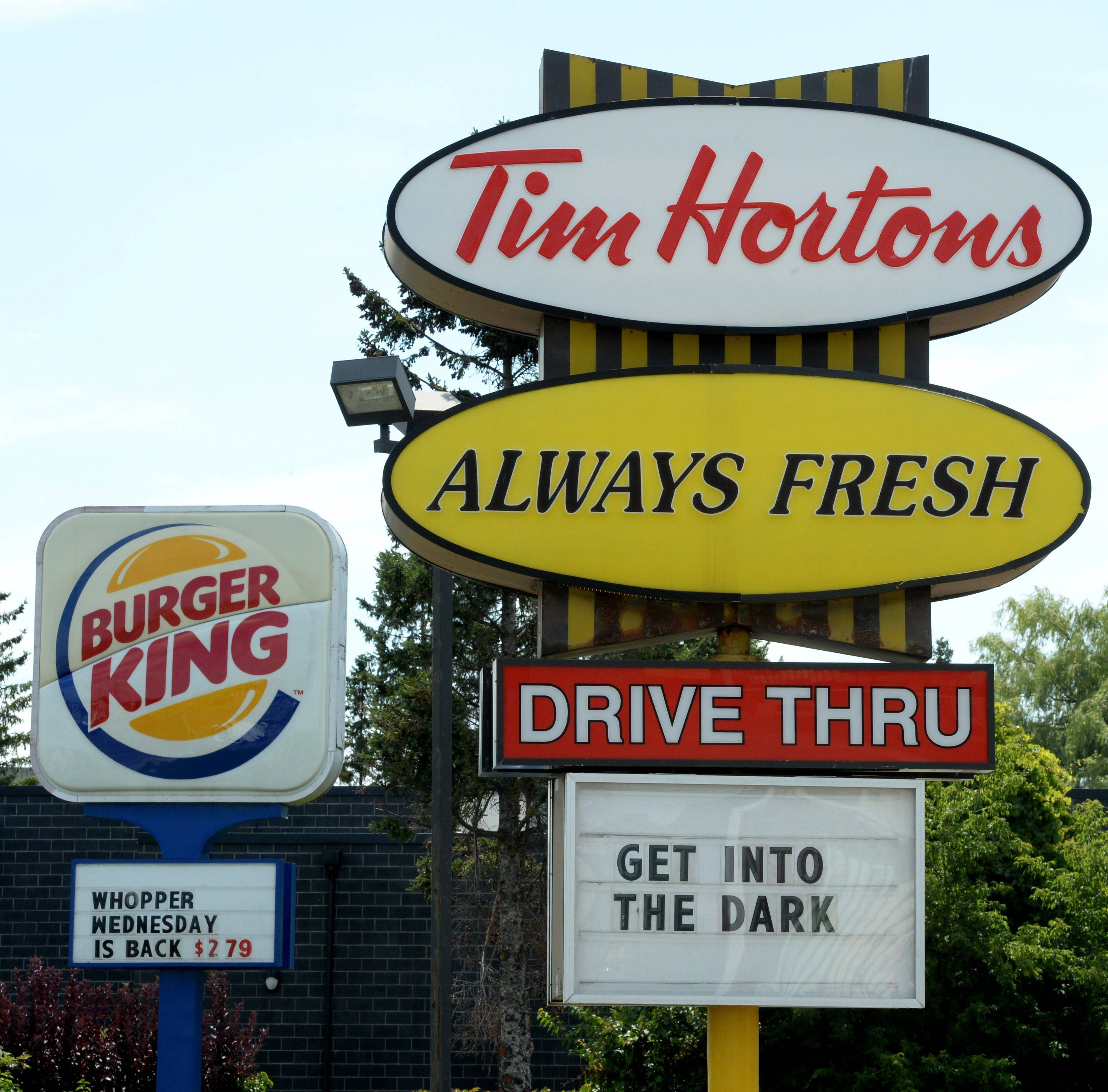 A Burger King sign and a Tim Hortons sign are displayed on St. Laurent Boulevard in Ottawa, Canada. Canada's iconic coffee chain, Tim Hortons, and Miami-based Burger King say they will join forces but will operate as independent brands to form the world's third-largest quick service restaurant company.