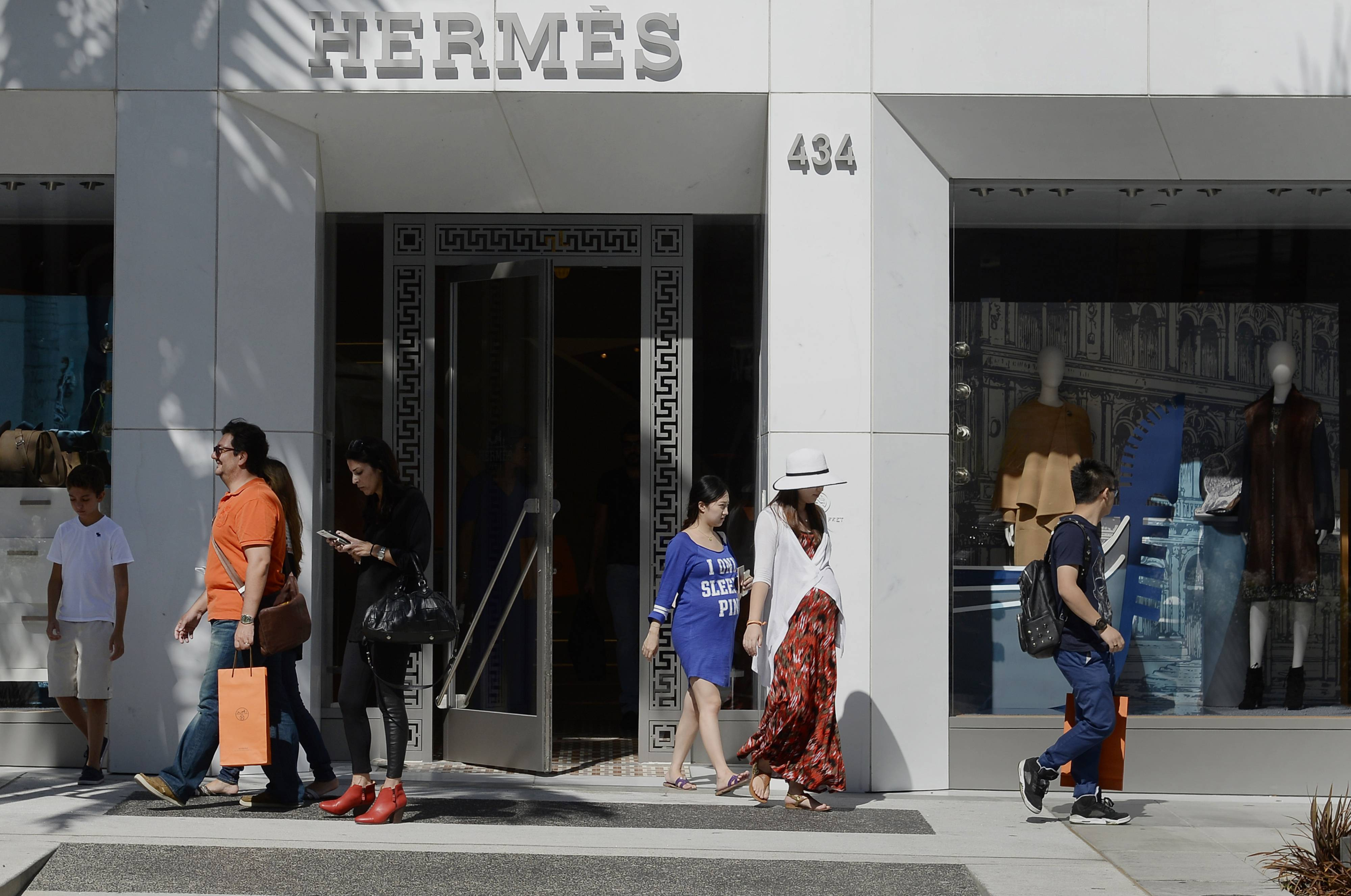 Shoppers exit a Hermes International SCA luxury goods store on Rodeo Drive in Beverly Hills. Consumer confidence in the U.S. unexpectedly climbed in August to the highest level in almost seven years, reinforcing signs of a strengthening outlook for the second half of 2014.