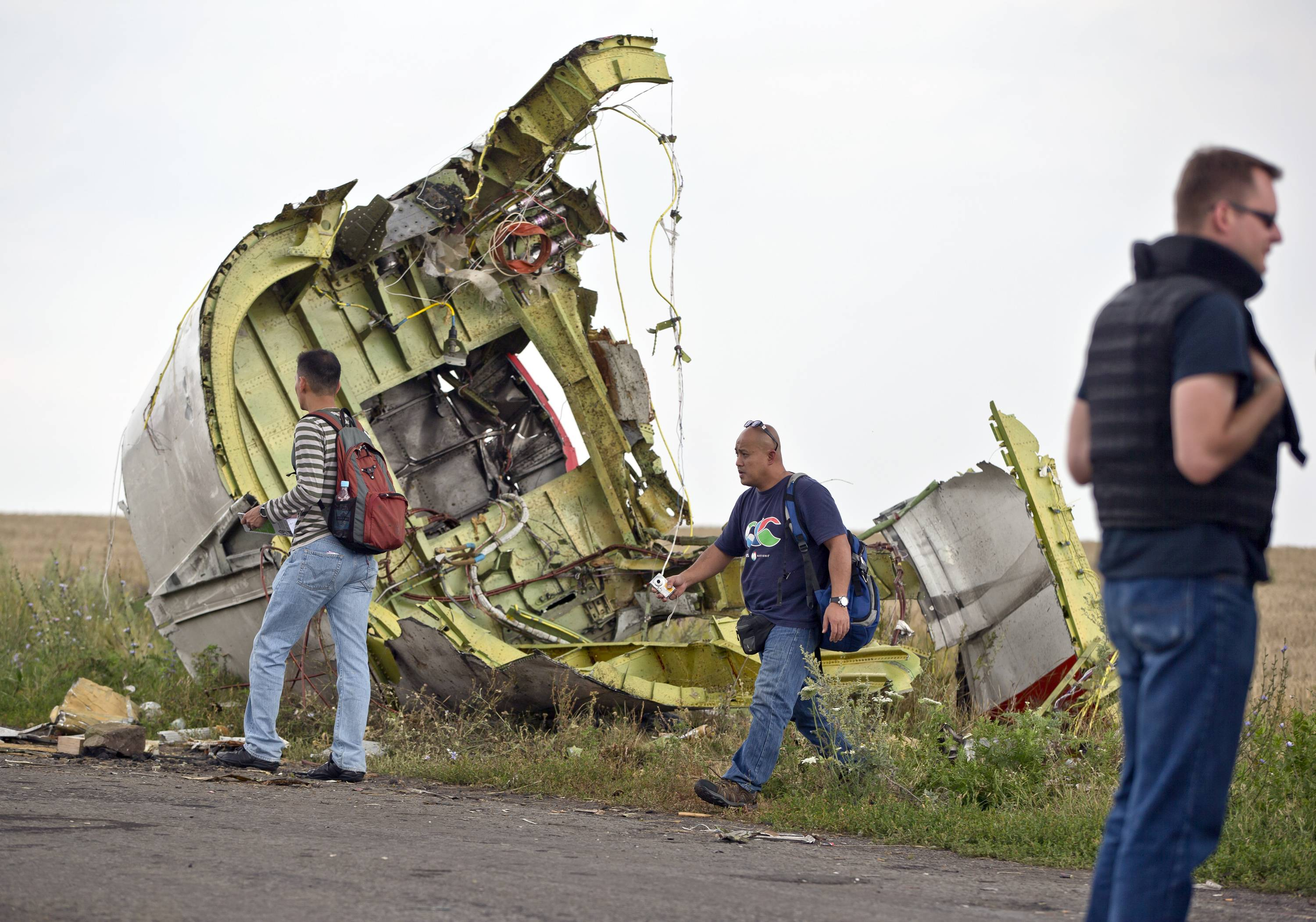 Malaysian air crash investigators walk by wreckage at the crash site of Malaysia Airlines Flight 17 near the village of Hrabove, eastern Ukraine last July. Families of passengers who were on the Malaysia Airlines plane shot down over Ukraine are starting to sort through the long process of gaining compensation for their loss.
